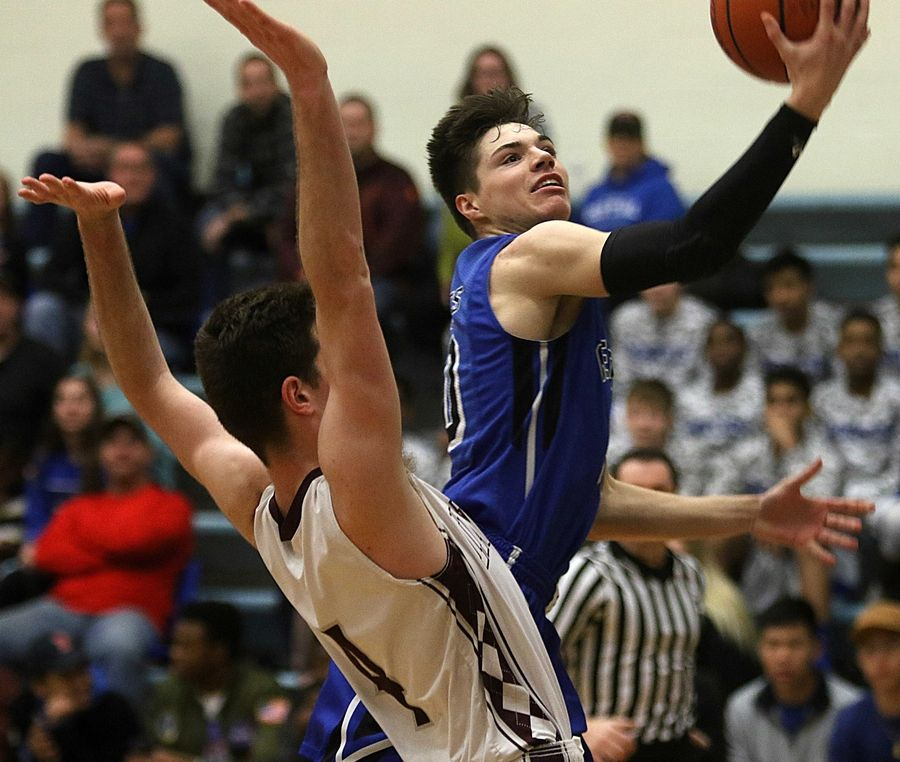 Burlington Central's Michael Kalusa soars past Marengo's Alexander Schirmer during the title game of the MLK Classic tournament at Burlington Monday night.