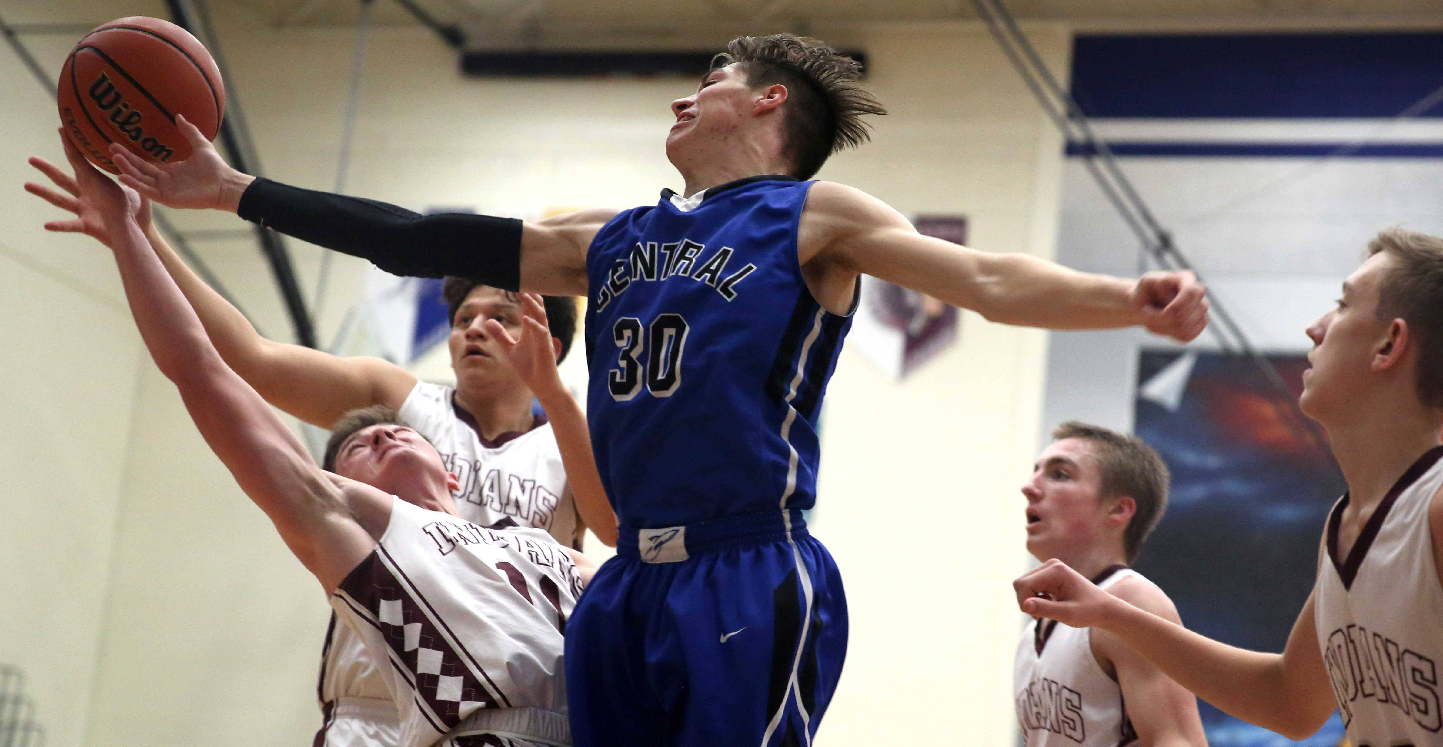 Burlington Central's Michael Kalusa, center, grabs a rebound against Marengo during the title game of the MLK Classic tournament at Burlington Monday night.