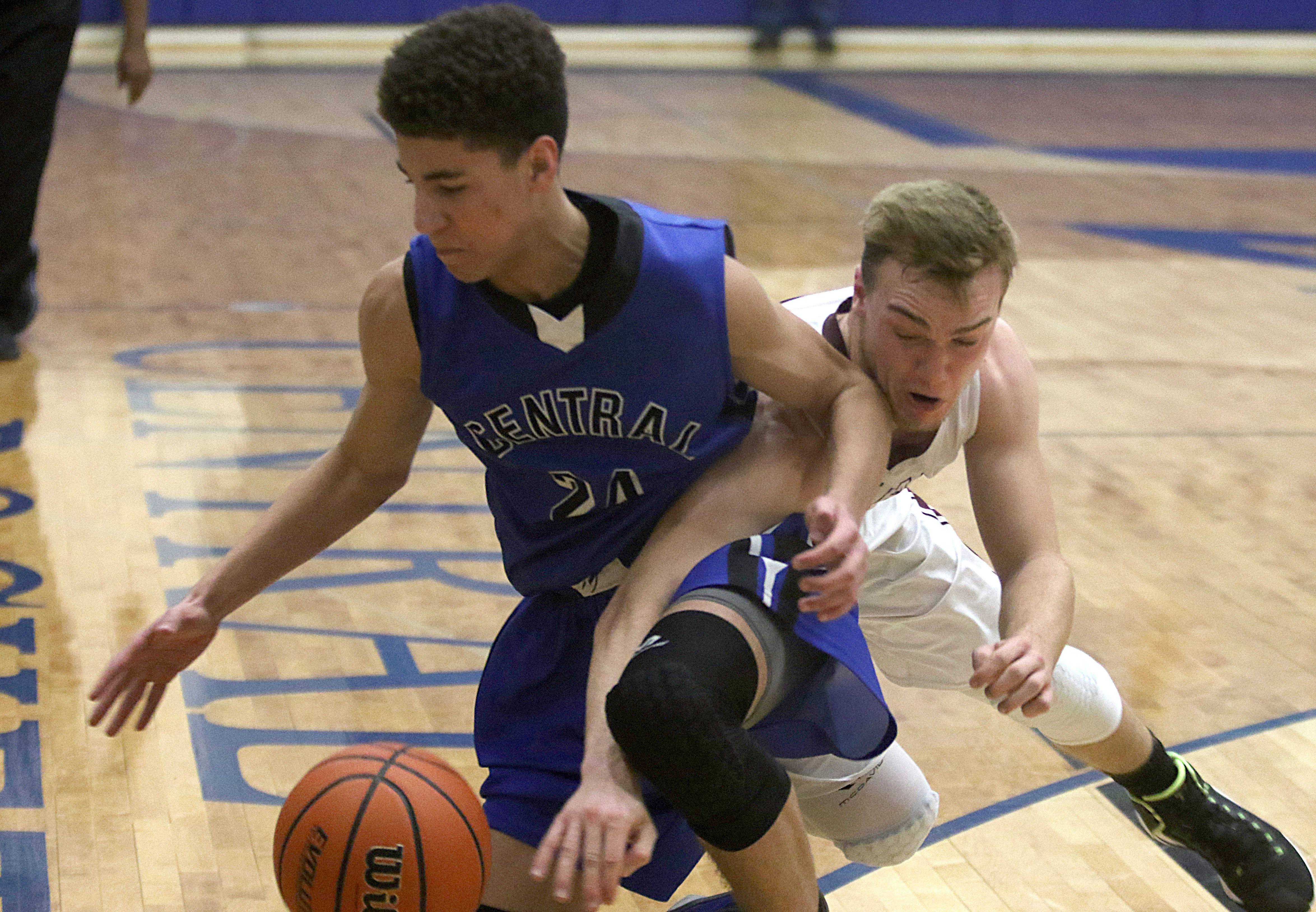 Burlington Central's Patrick Mayfield, left, battles Marengo's Connor Wascher for the ball during the title game of the MLK Classic tournament at Burlington Monday night.