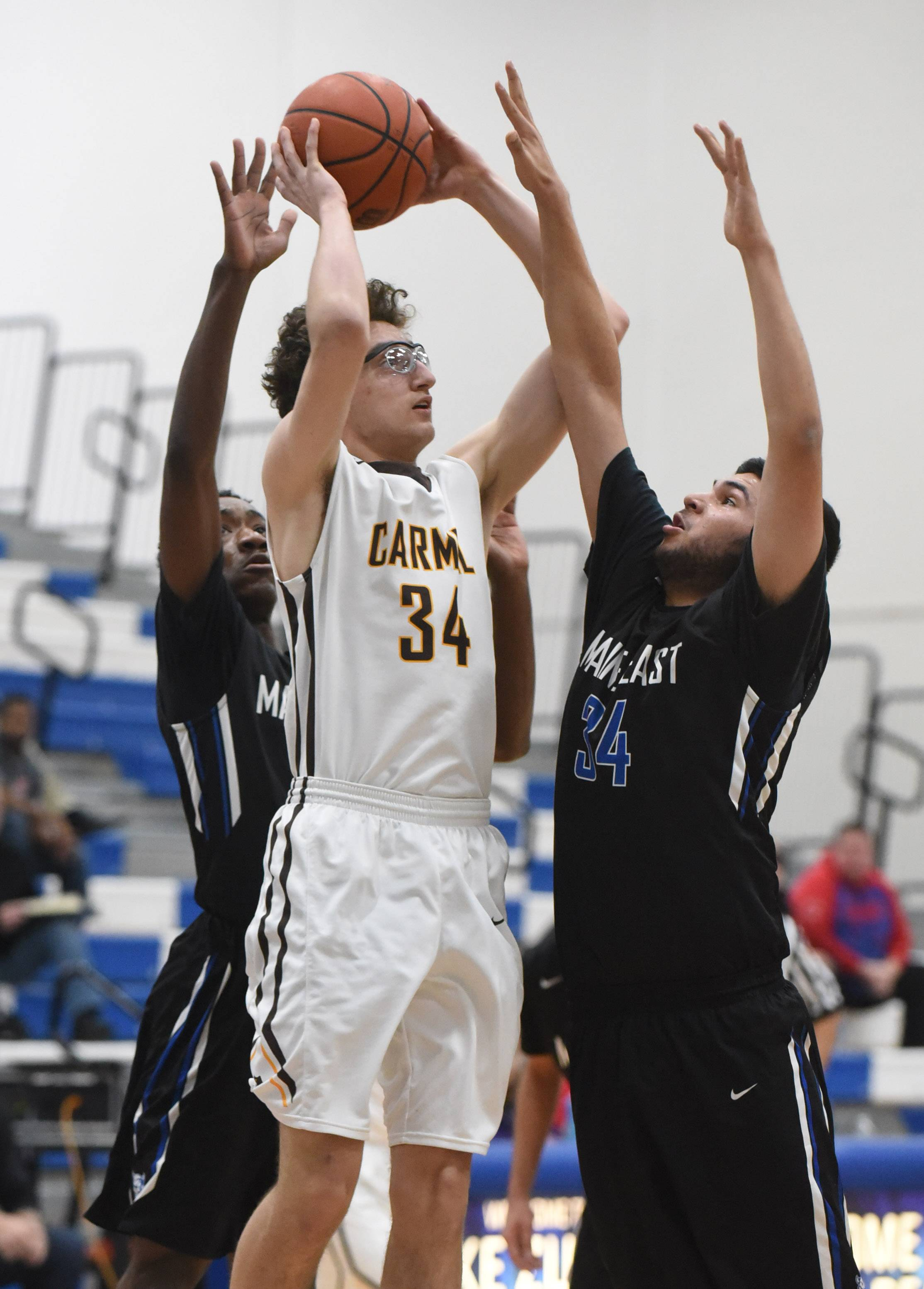 Carmel's Johnny Roeser (34) takes a shot over Maine East's Kyle Gilani during Monday's MLK tournament at Lake Zurich.