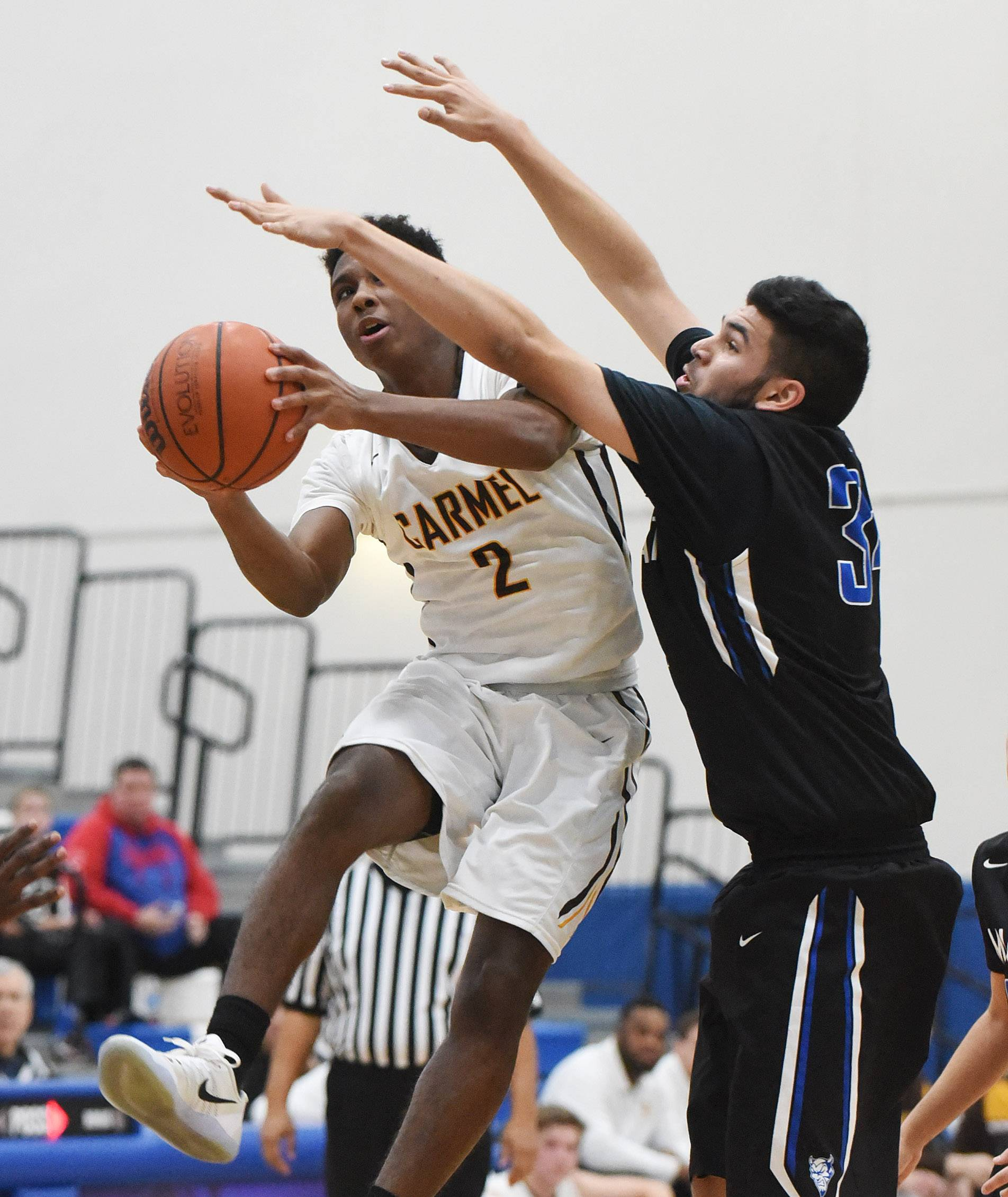 Carmel's Brian Julien (2) heads to the hoop past Maine East's Kyle Gilani during MLK tournament play Monday at Lake Zurich.