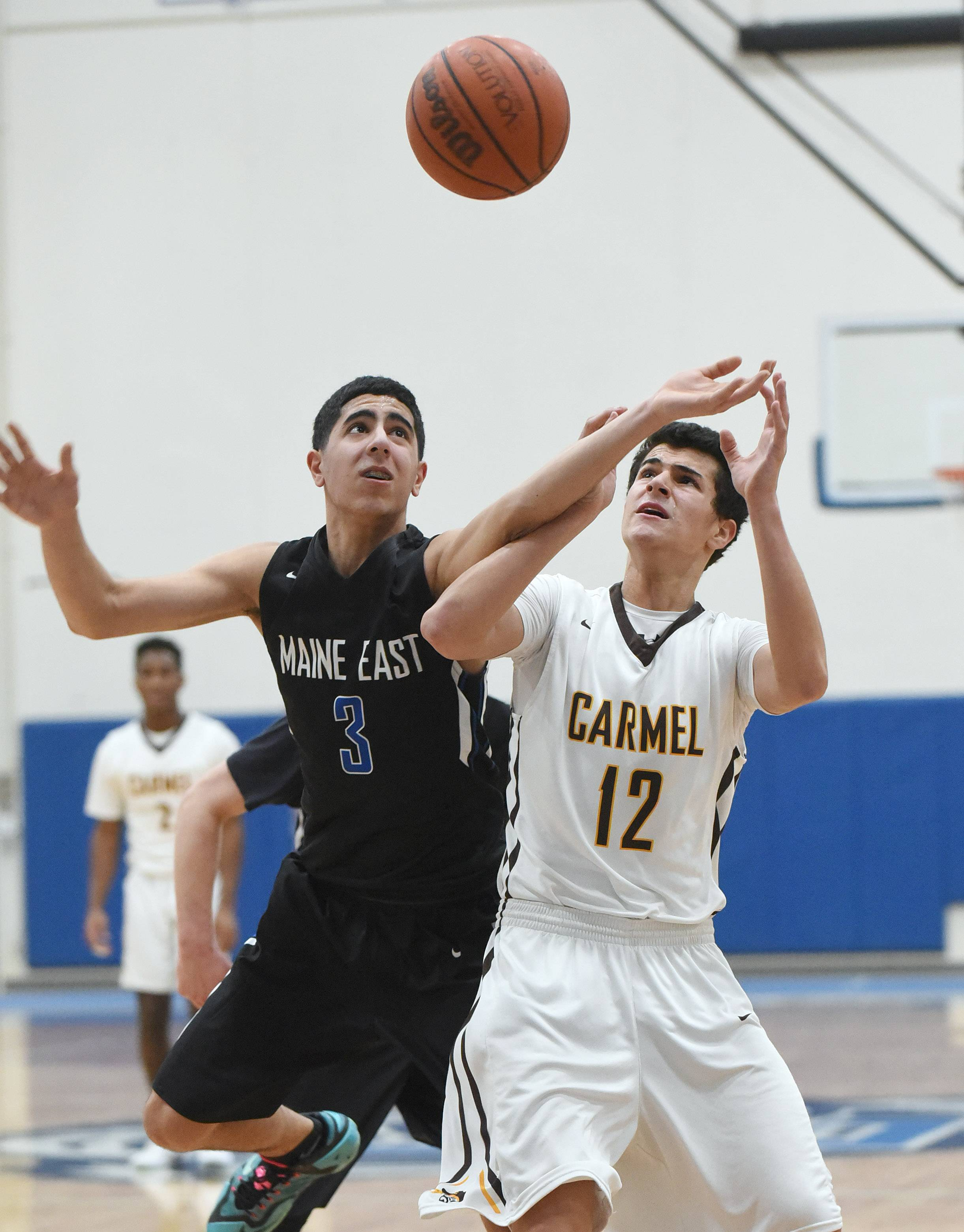 Maine East's Ali Sabet (3) and Carmel's Evan Myers (12) eye the rebound during Monday's MLK tournament at Lake Zurich.