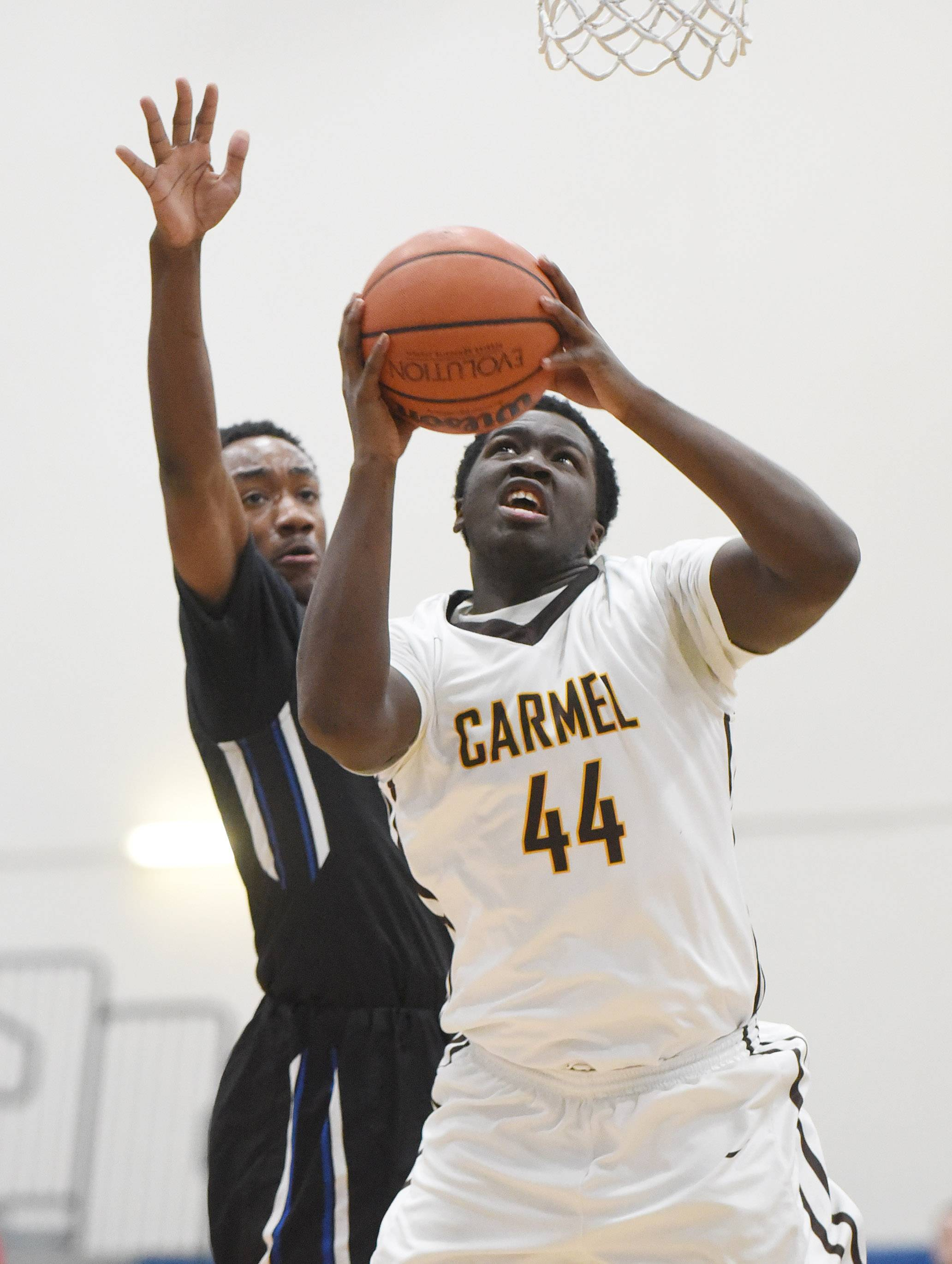 Carmel's Jalen Snell (44) takes a shot past Maine East's Nathanael Vangine at Monday's MLK tournament at Lake Zurich.