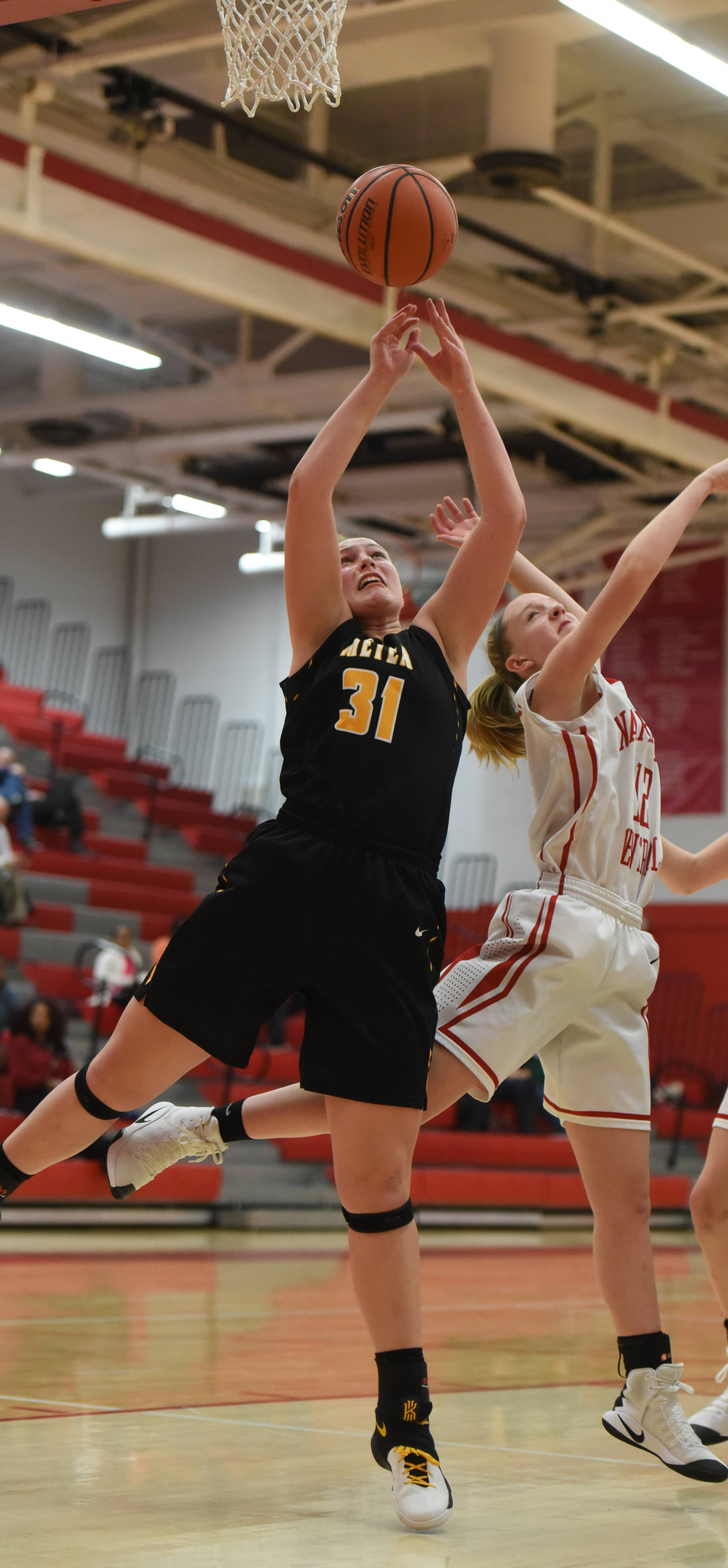 Metea Valley's Ashley Konkle (31) and Naperville Central's Abigail Kincaide (12) vie for a rebound during the Metea Valley at Naperville Central girls basketball game Thursday.