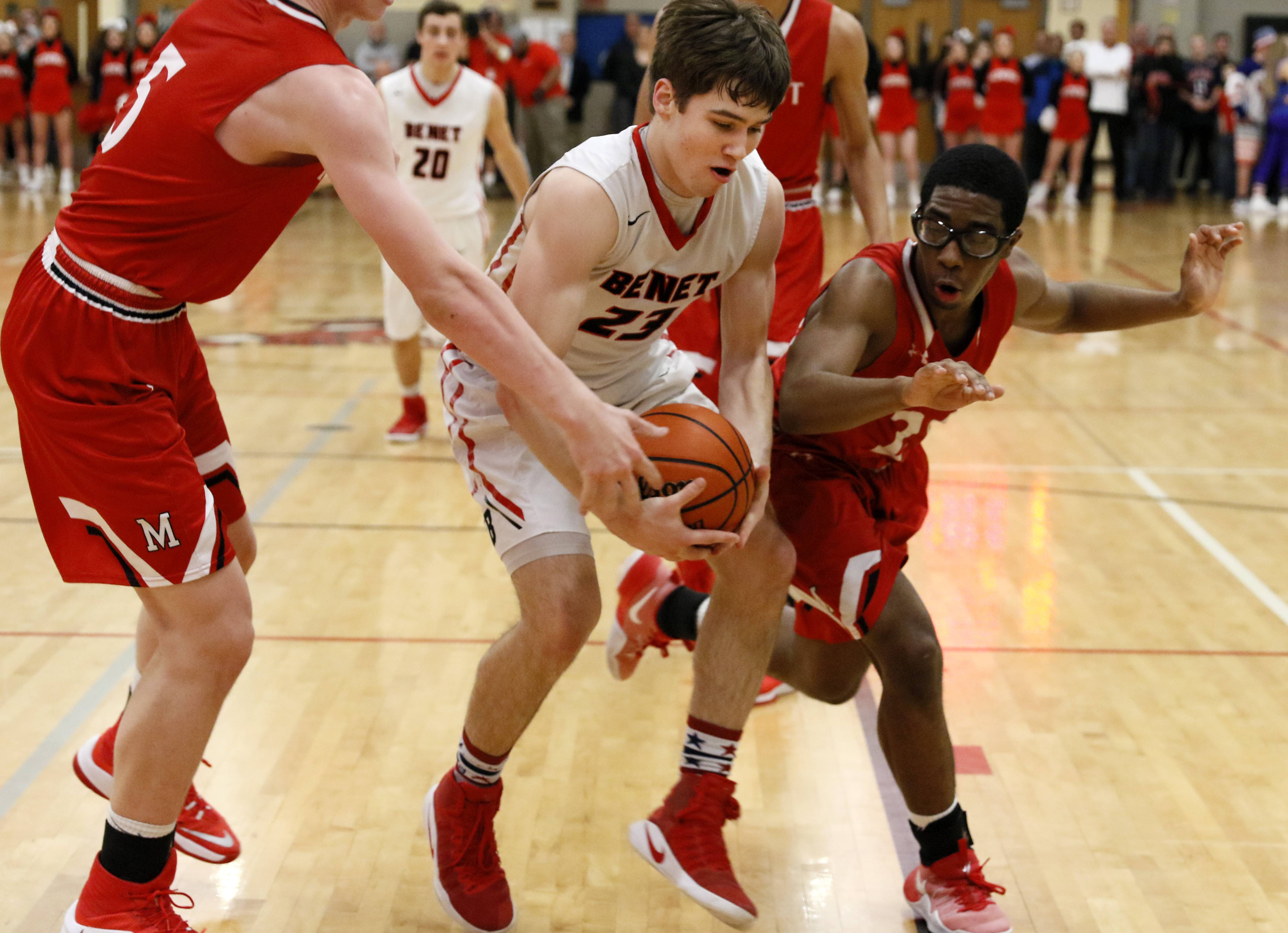 Benet Academy's Liam Lyman, center, retrieves a loose ball against Marist defenders during boys basketball action in Lisle.