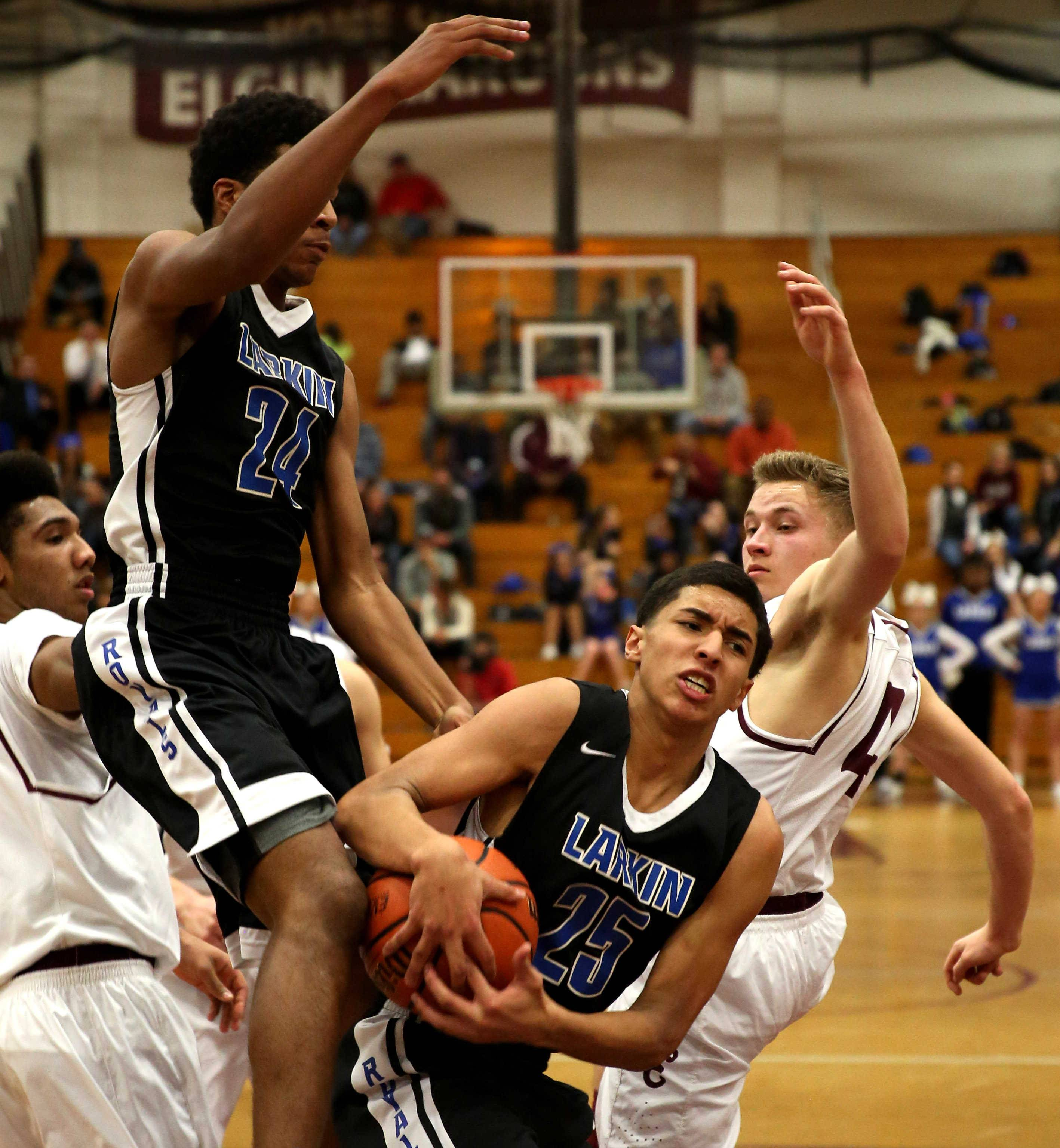 Larkin's Victor Perez, front, secures a rebound against Elgin during varsity boys basketball at Chesbrough Field House on the campus of Elgin High School Friday night.