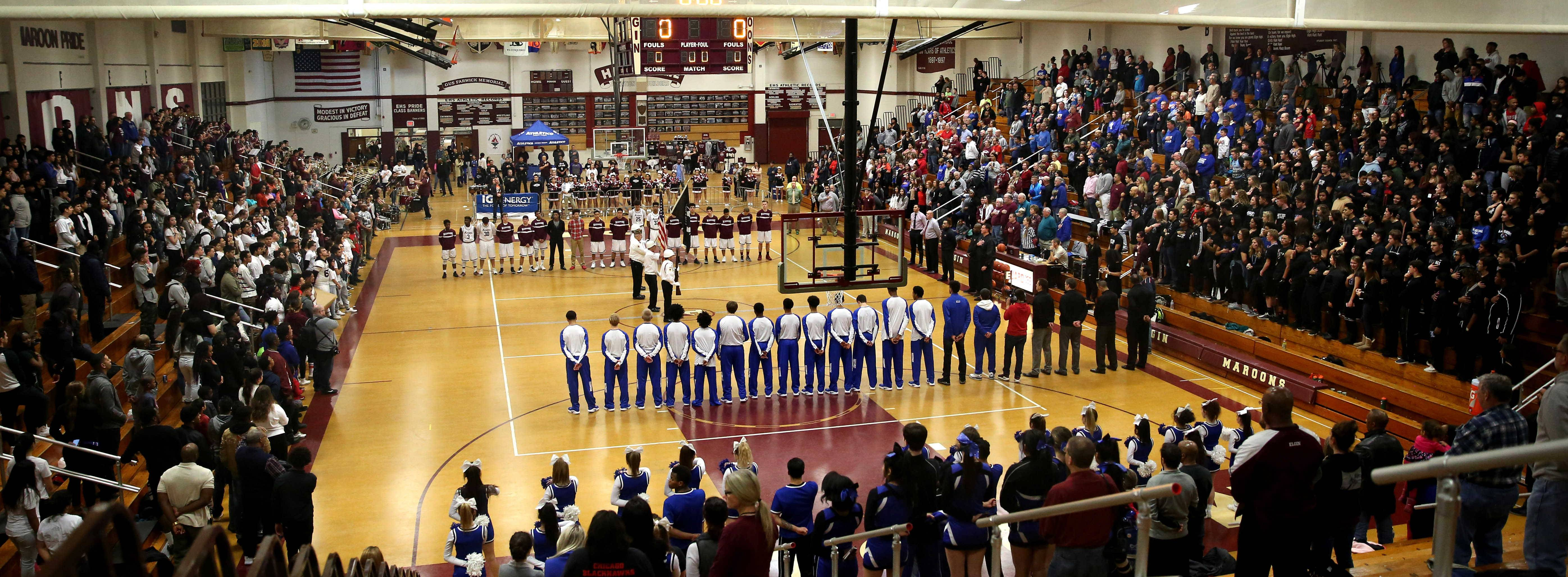 A full house stands as the color guard assembles at center court for the national anthem before crosstown varsity boys basketball action between Elgin and Larkin at Chesbrough Field House on the campus of Elgin High School Friday night.