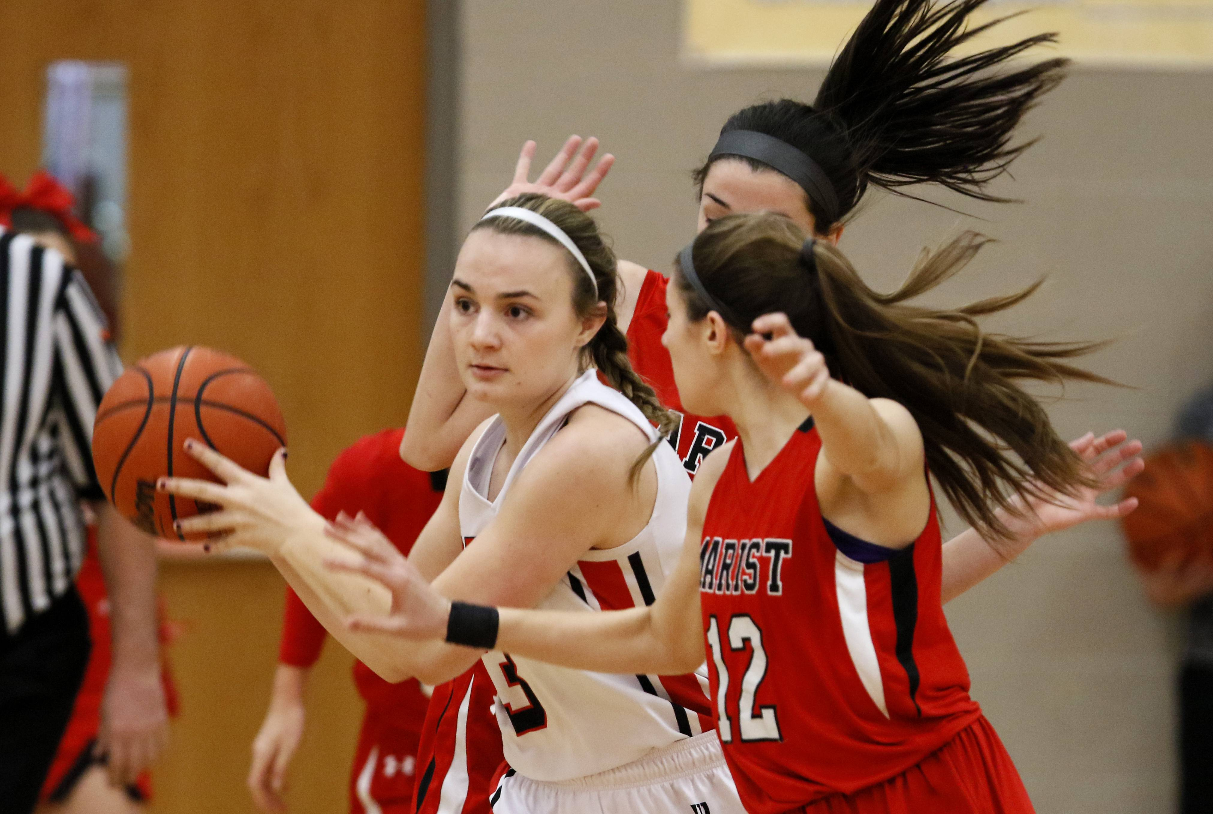 Benet Academy's Ali Kramer, left, pushes the ball up court against Marist during girls basketball action in Lisle.