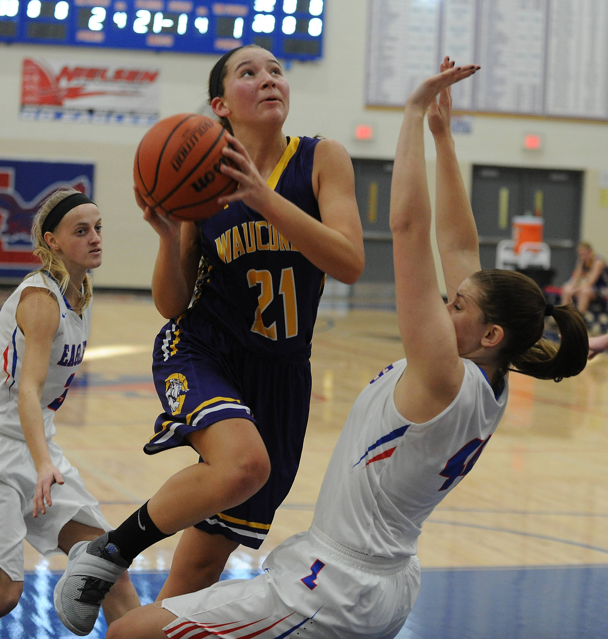 Mark Welsh/mwelsh@dailyherald.comWauconda's Allie Tylka collides with Lakes' Natalie Pawlak while eyeing the basket in the first half at Lakes on Saturday.