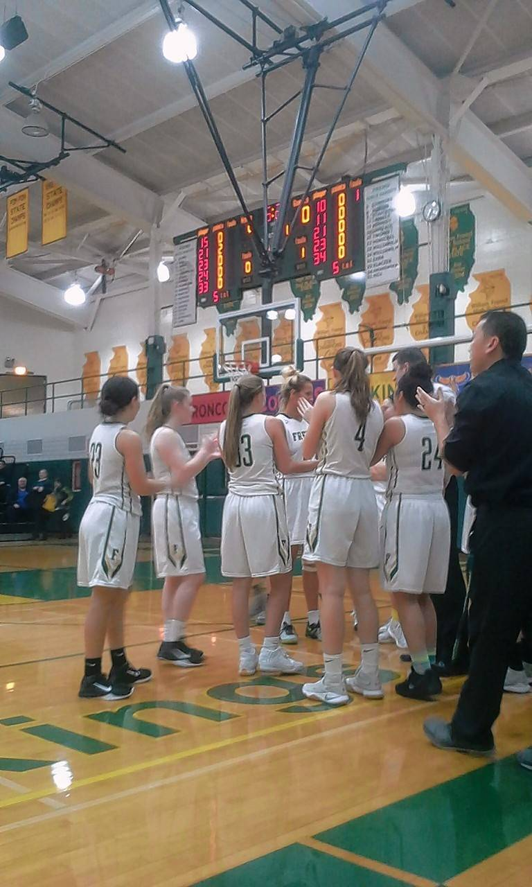 Fremd girls basketball players applaud teammate Grace Tworek after she scored her 1,000th career point early in Tuesday's game against Palatine.