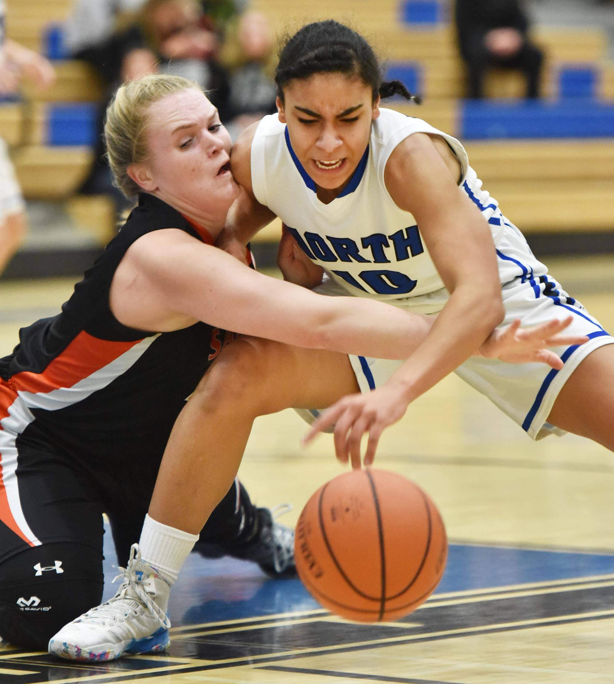 St. Charles North's Jazmyn Harmon fights against St. Charles East's Sara Rosenfeldt for control of the ball Tuesday at North High School in St. Charles.