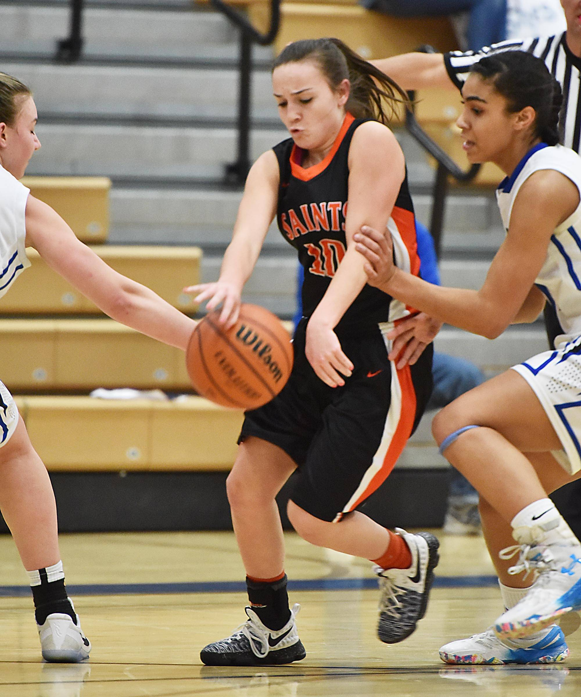 St. Charles East's Marissa Urso drives through the defense of St. Charles North's Elizabeth Olsem and Jazmyn Harmon Tuesday at North High School in St. Charles.