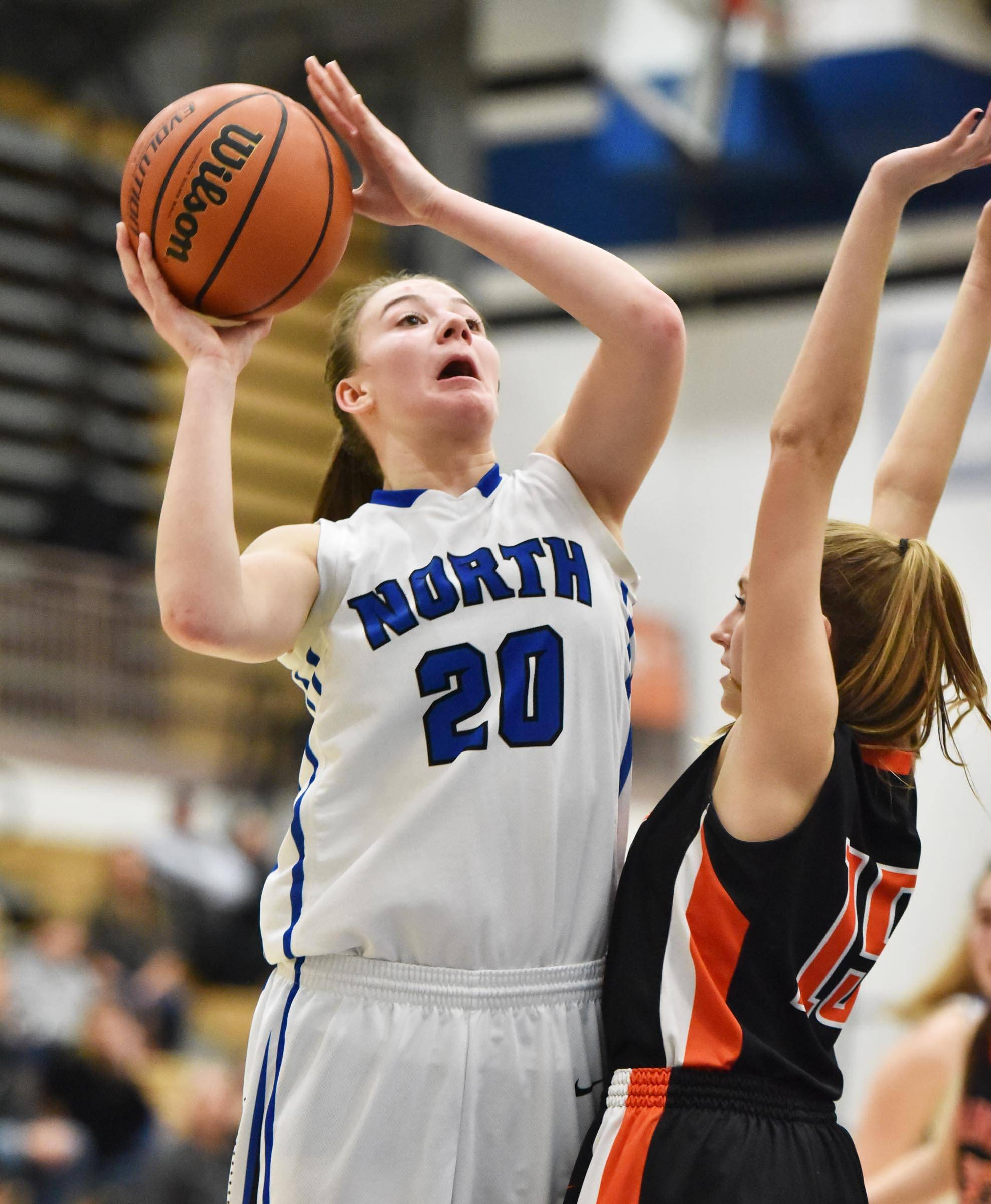 St. Charles North's Elizabeth Olsem goes up for a shot against St. Charles East's Nicole Jordan Tuesday at North High School in St. Charles.