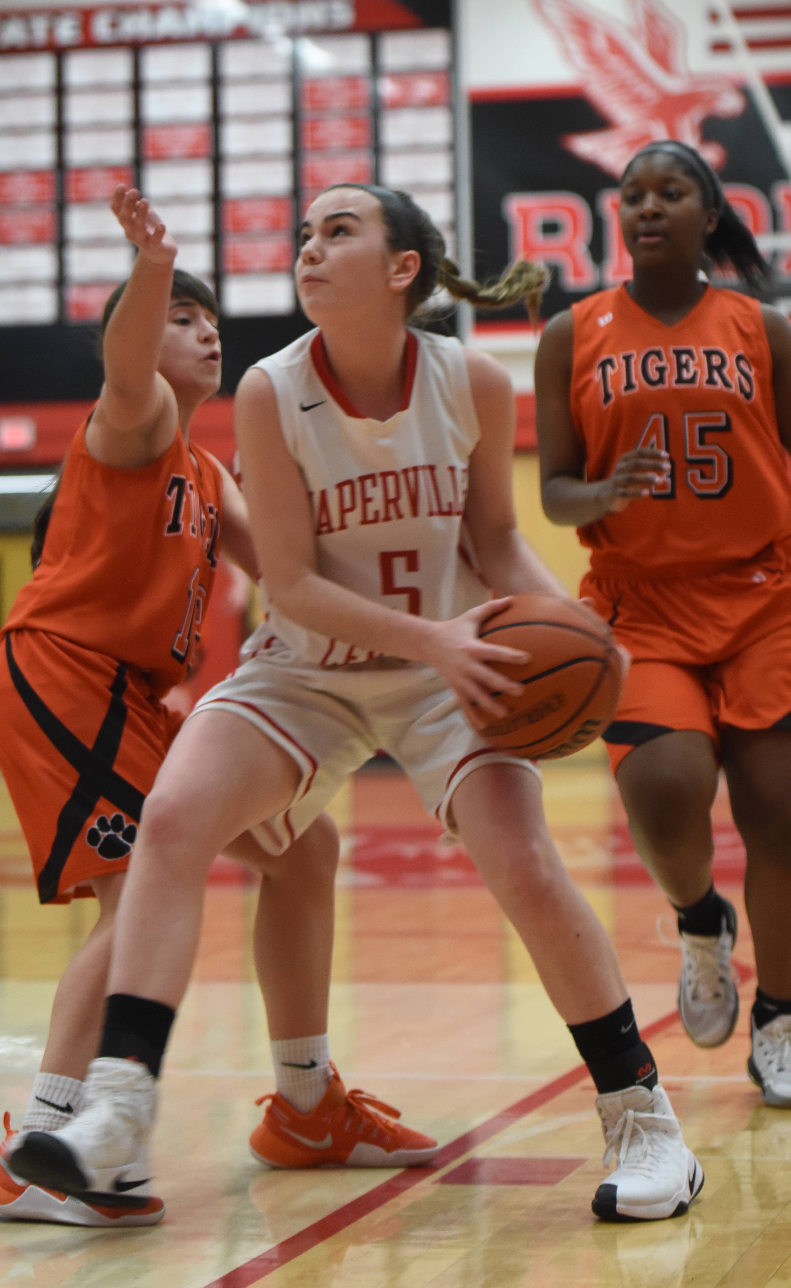 Wheaton Warrenville South's Mira Emma (12) tries to block Naperville Central's Erin Moran (05) as she looks to pass. This took place during the Wheaton Warrenville South at Naperville Central girls basketball game Thursday.