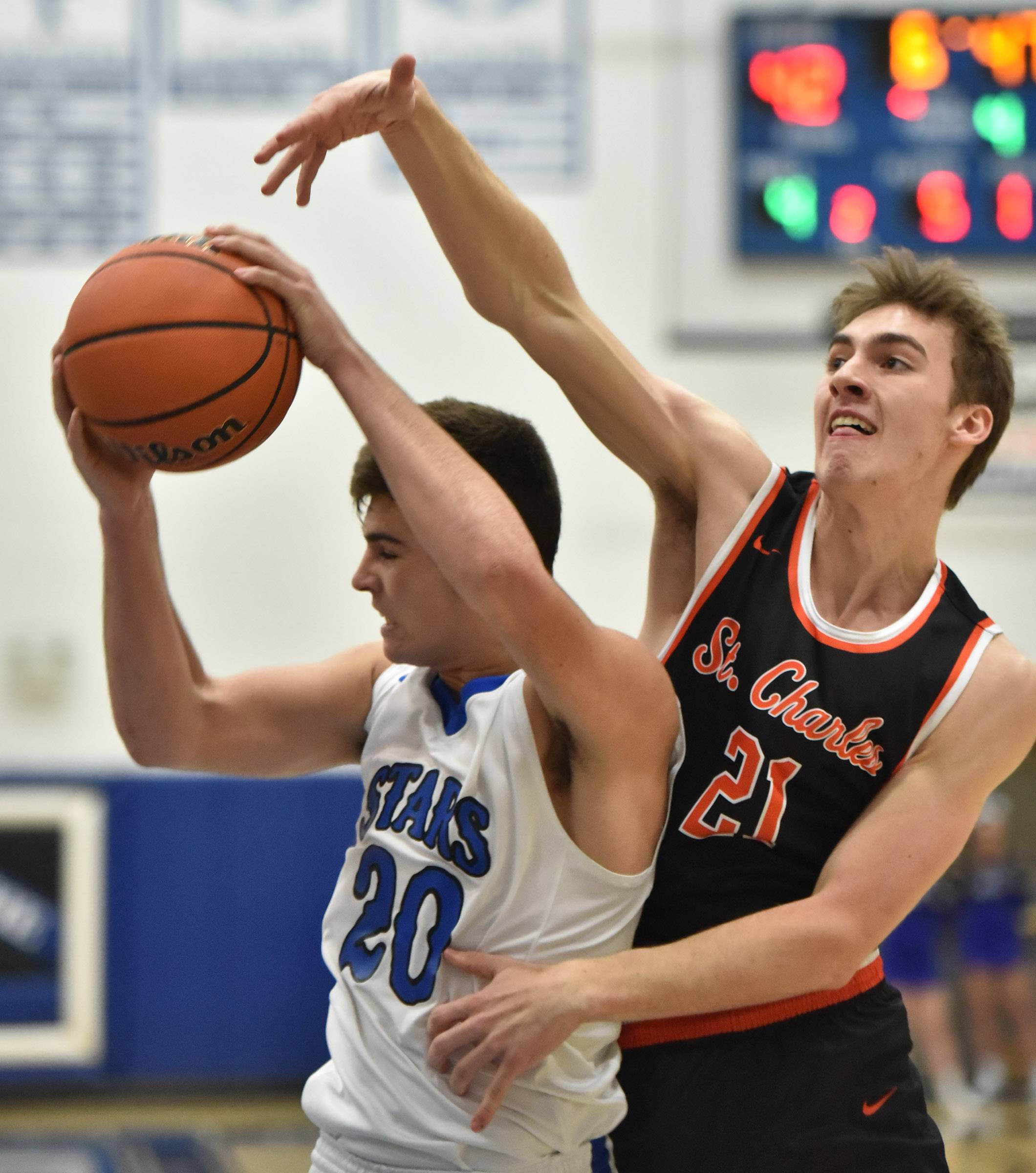 St. Charles North's Kyle King pulls in a rebound against St. Charles East's Wade Kyle Tuesday in St. Charles.