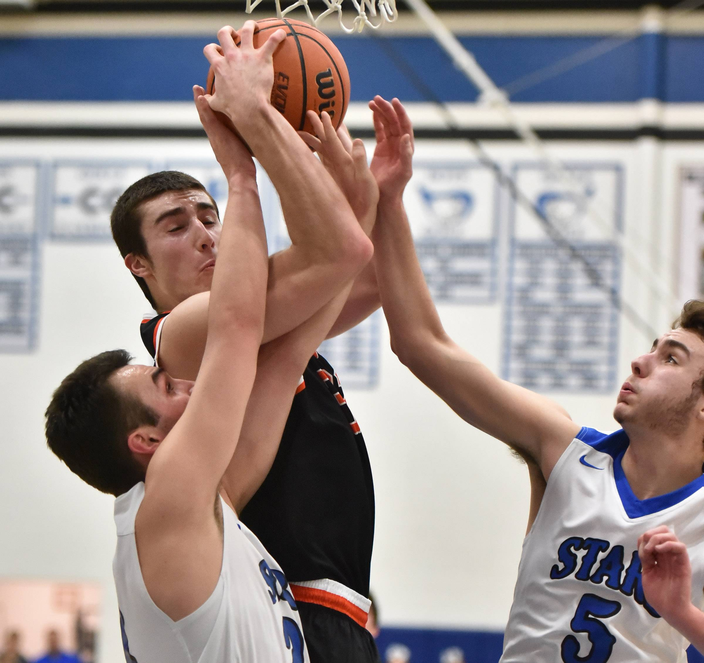 St. Charles East's Justin Hardy secures a rebound between St. Charles North's Ryan Callaghan and Brendan Dal Degan Tuesday in St. Charles.