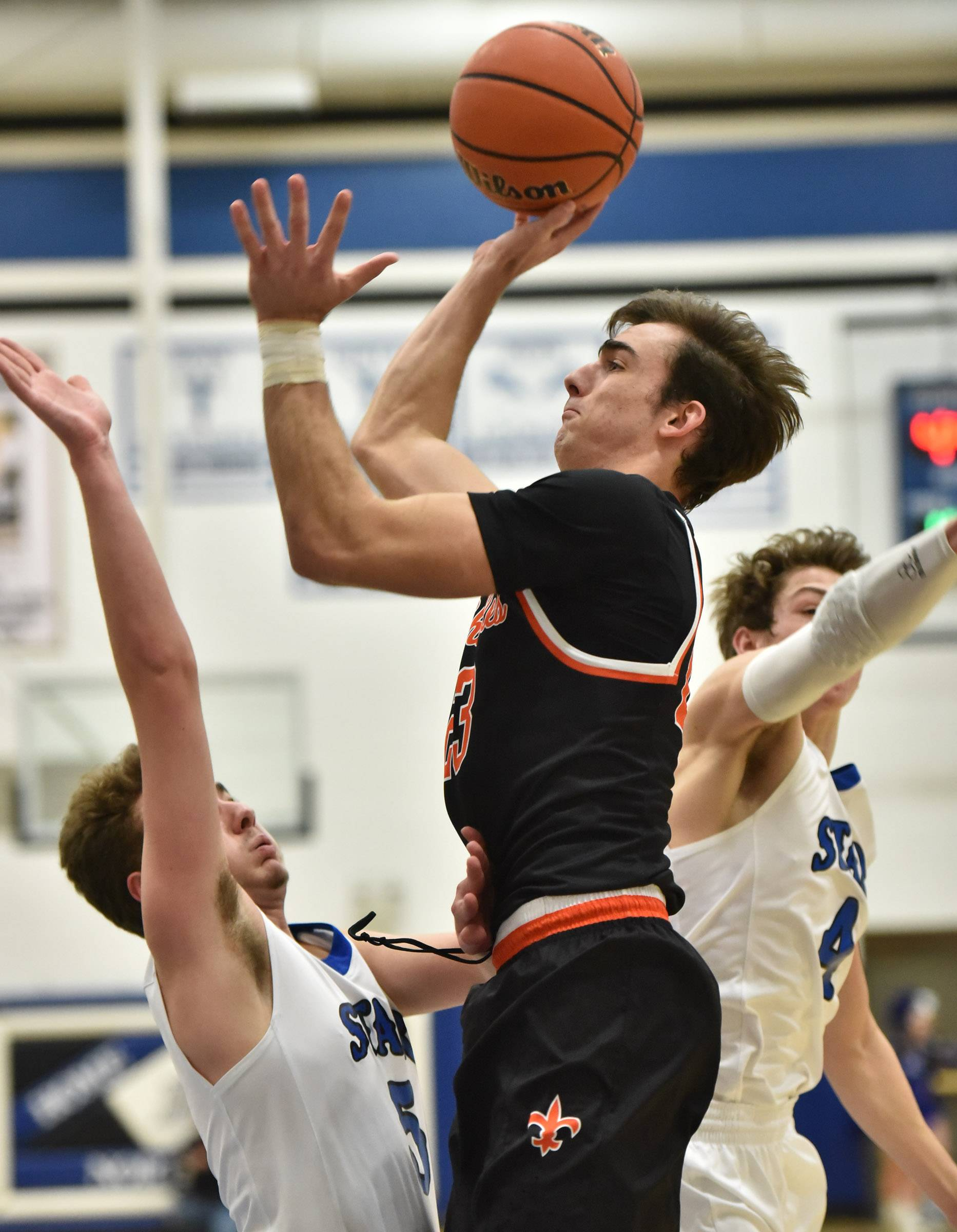 St. Charles East's Zachary Mitchell shoots against St. Charles North's Brendan Dal Degan and Anthony Delisi Tuesday in St. Charles.