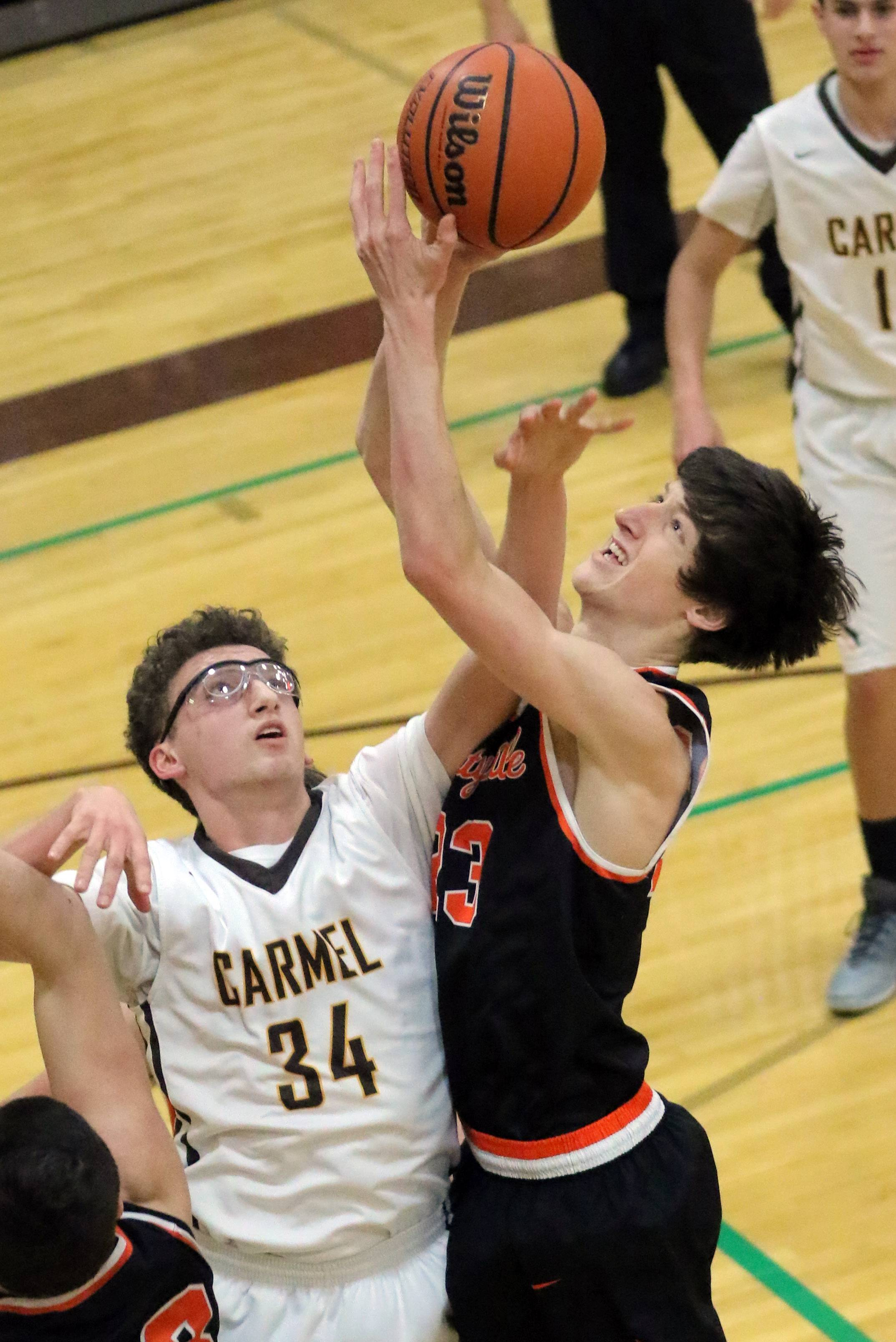 Carmel's Jonathan Roeser (34) and Libertyville's Drew Peterson battle for a rebound Tuesday night in Mundelein.
