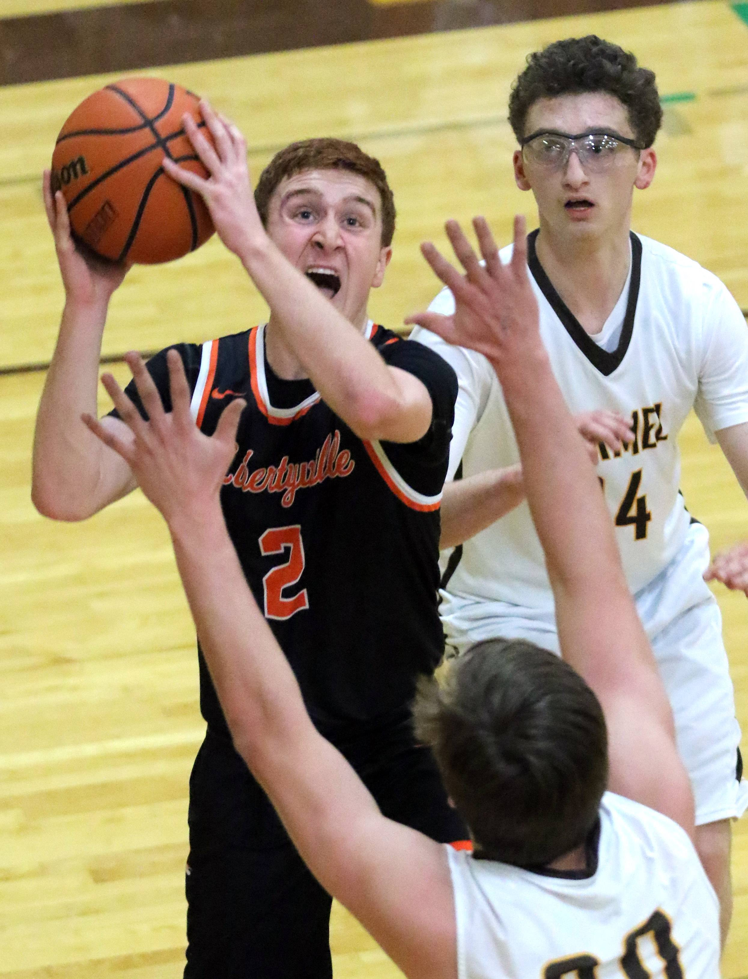 Libertyville's Ryan Wittenbrink, left, drives on Carmel's Jonathan Roeser and Lukas Galdoni on Tuesday night in Mundelein.