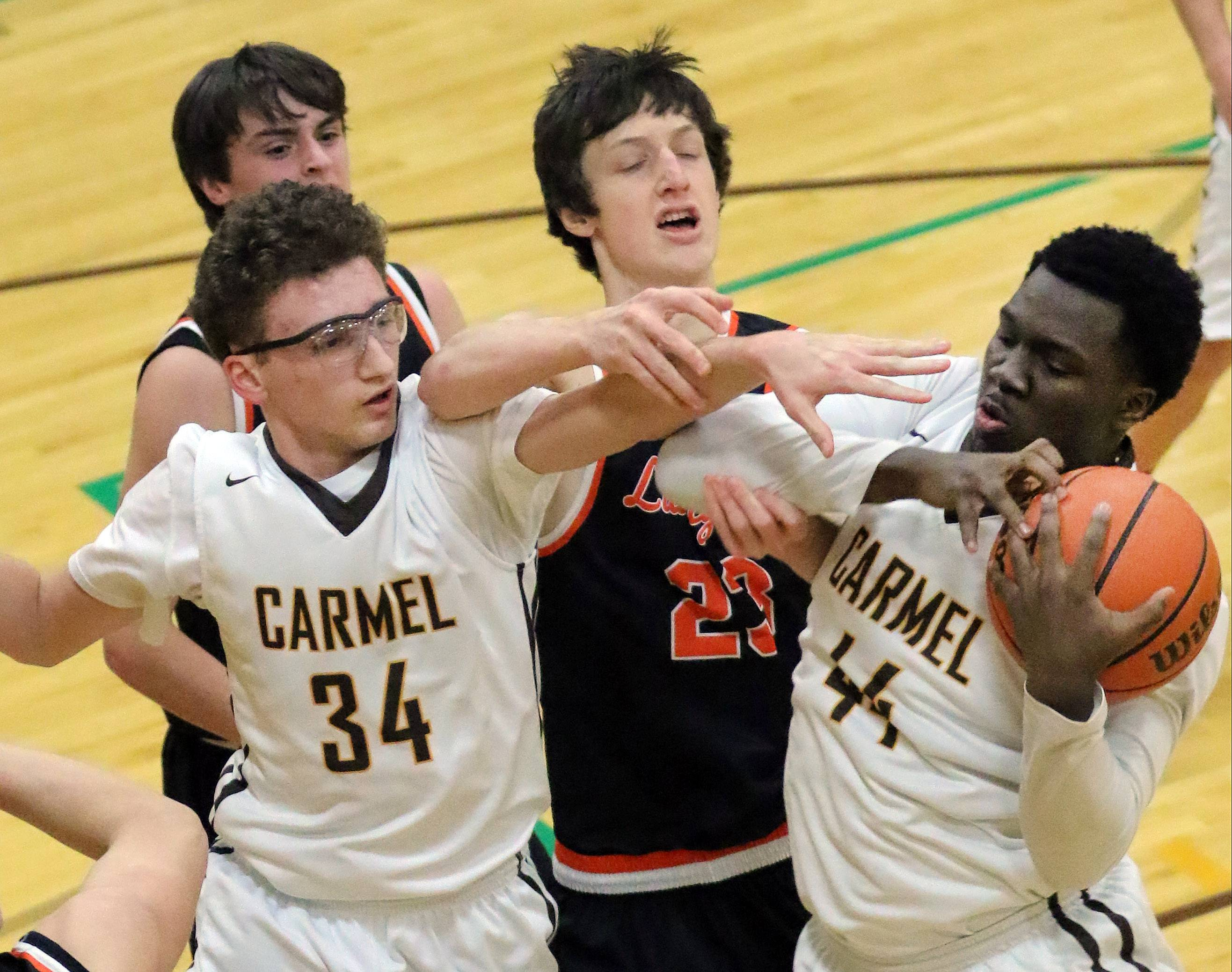 From left, Carmel's Jonathan Roeser (34), Libertyville's Drew Peterson and Carmel's Jalen Snell battle for a rebound Tuesday night in Mundelein.