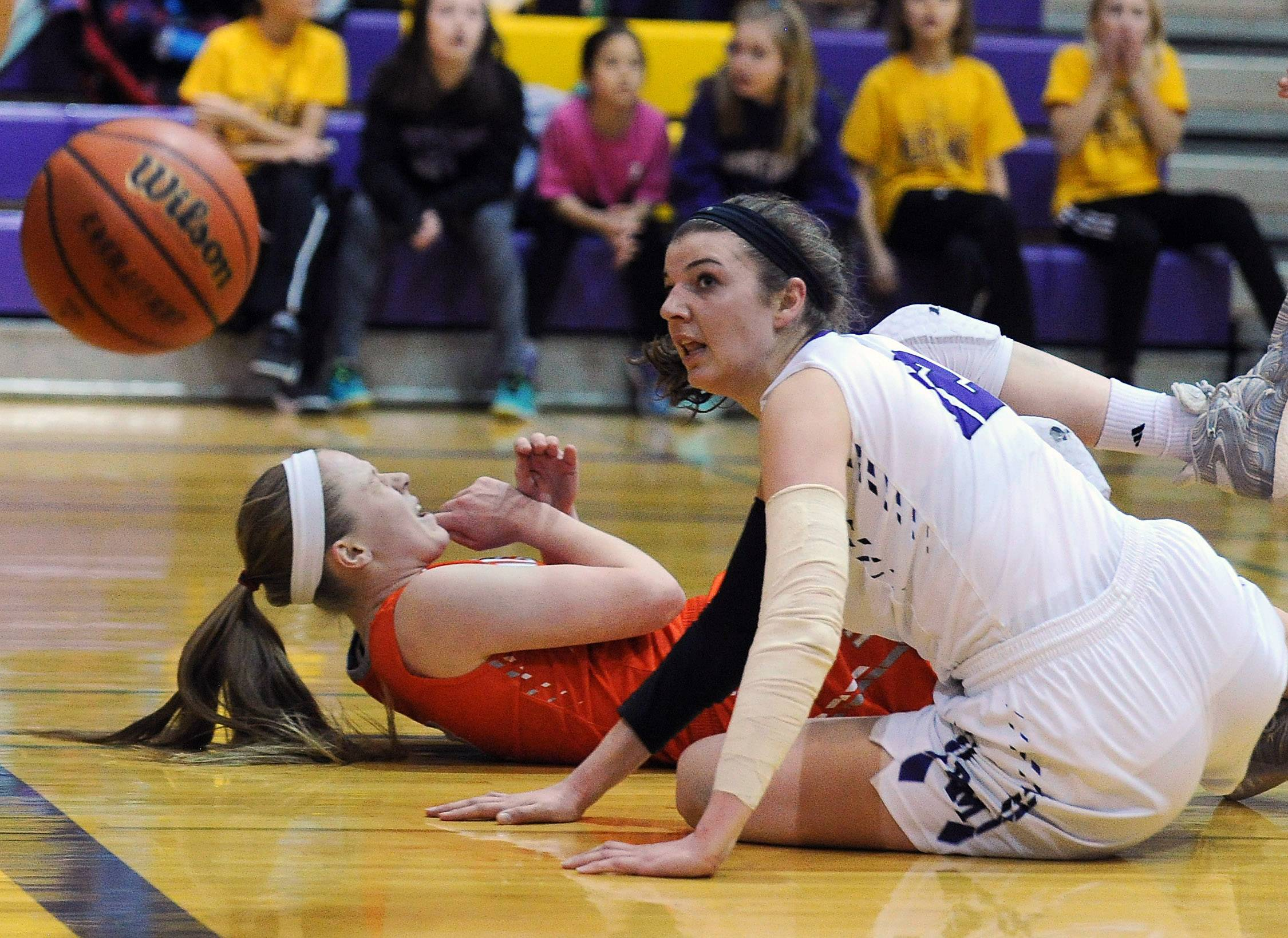Hersey's Claire Gritt hits the floor brought down by Meadow's Morgan Campagna in the girls basketball game at Meadows on Friday.