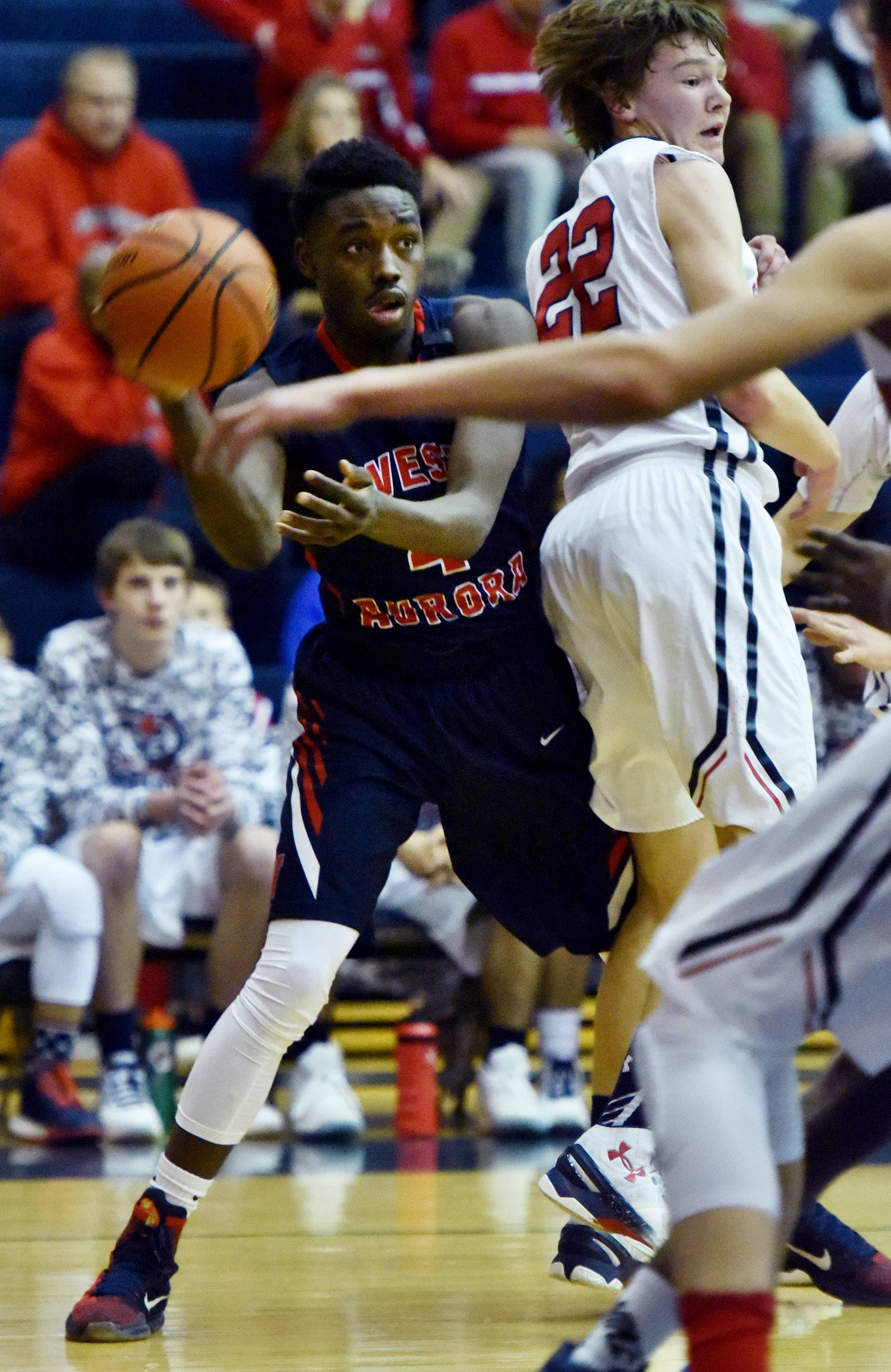 West Aurora's Dayshawnn Rogers passes around South Elgin's Noah Rohr Friday in South Elgin.
