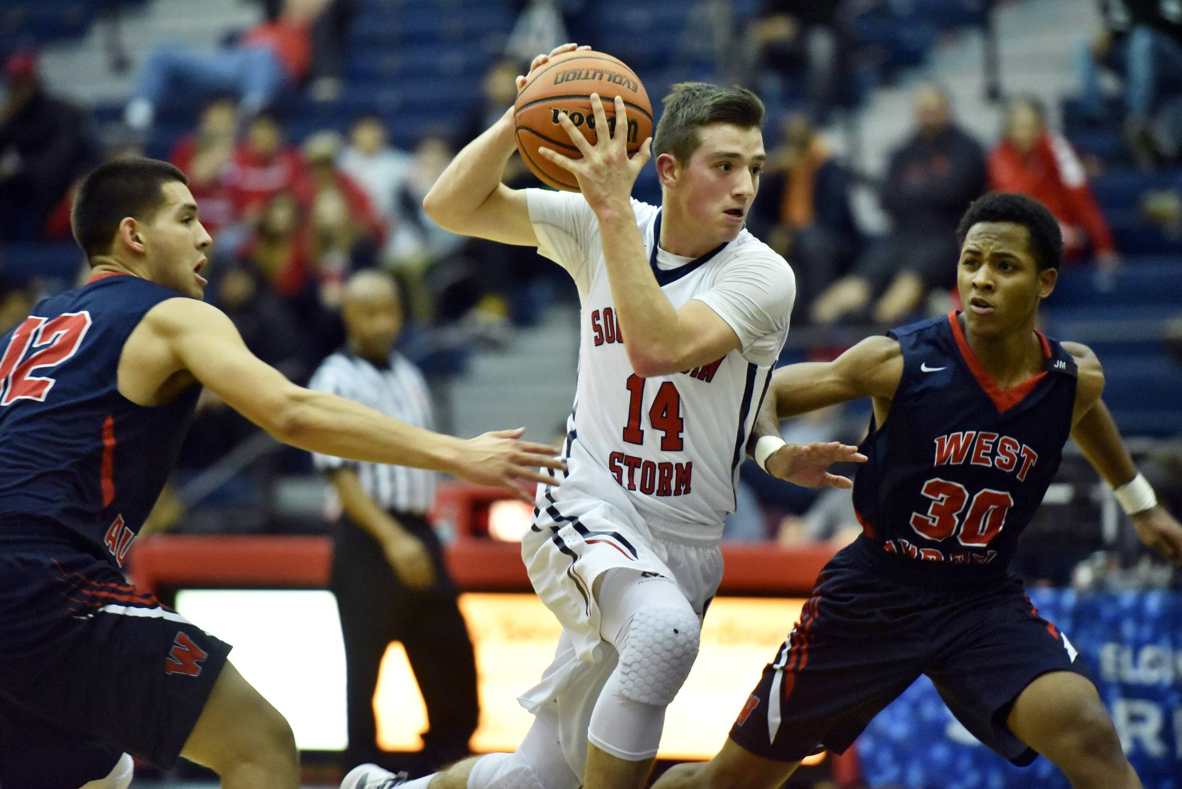 South Elgin's Kyle Scully drives between West Aurora's Damian Virgen and DaVion Cross Friday in South Elgin.
