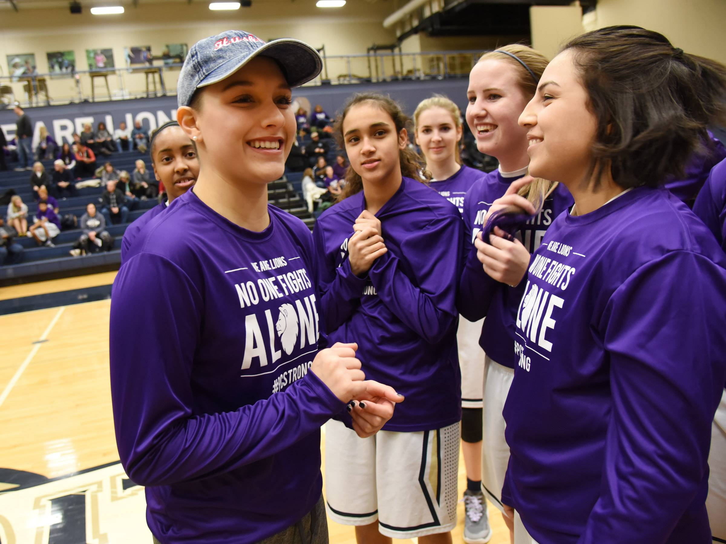 Harvest Christian Academy alumni Paulina Castro, left, is greeted by her former teammates before the girls basketball game Friday in Elgin. She is now a NIU freshman who is battling Hodgkin's lymphoma.