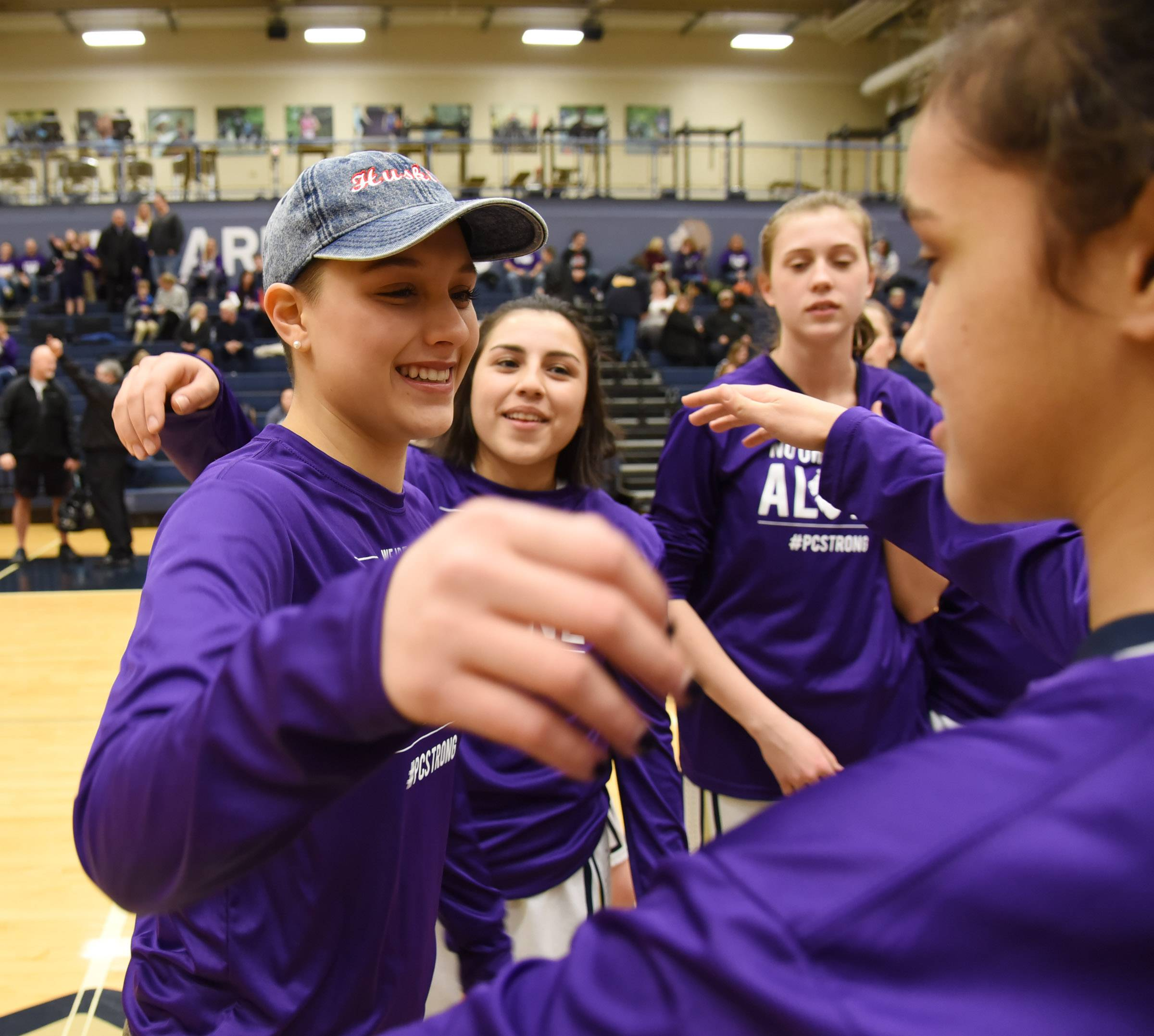 Harvest Christian Academy alumni Paulina Castro is greeted by her former teammates before the girls basketball game Friday in Elgin. She is now a NIU freshman who is battling Hodgkin's lymphoma.