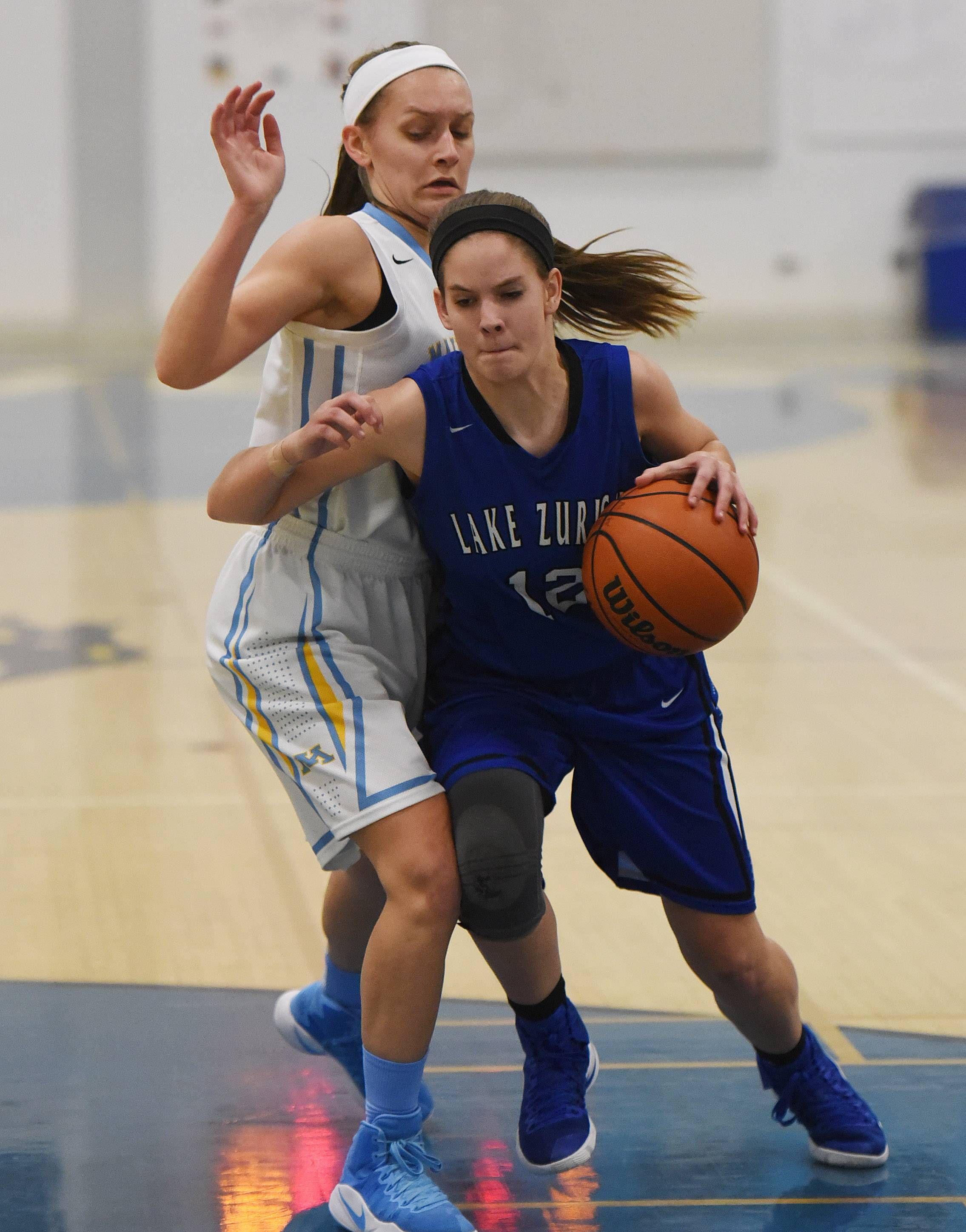 Lake Zurich's Brigid Ferguson, right, drives past Maine West's Catherine Johnson during Monday's game in Des Plaines.