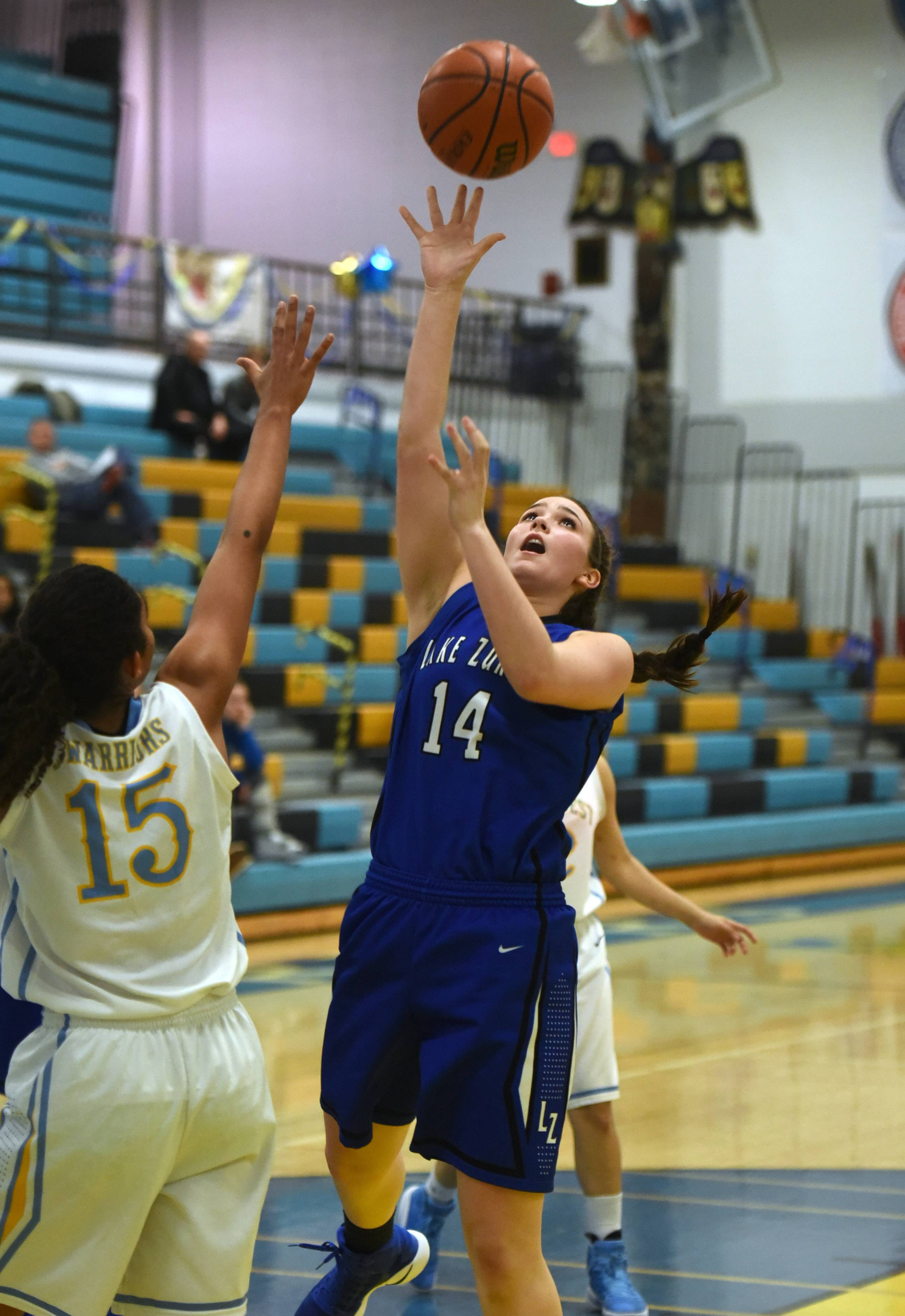 Lake Zurich's McKenna Zobel (14) takes a shot over Maine West's Rachel Kent (15) during Monday's girls basketball game in Des Plaines.