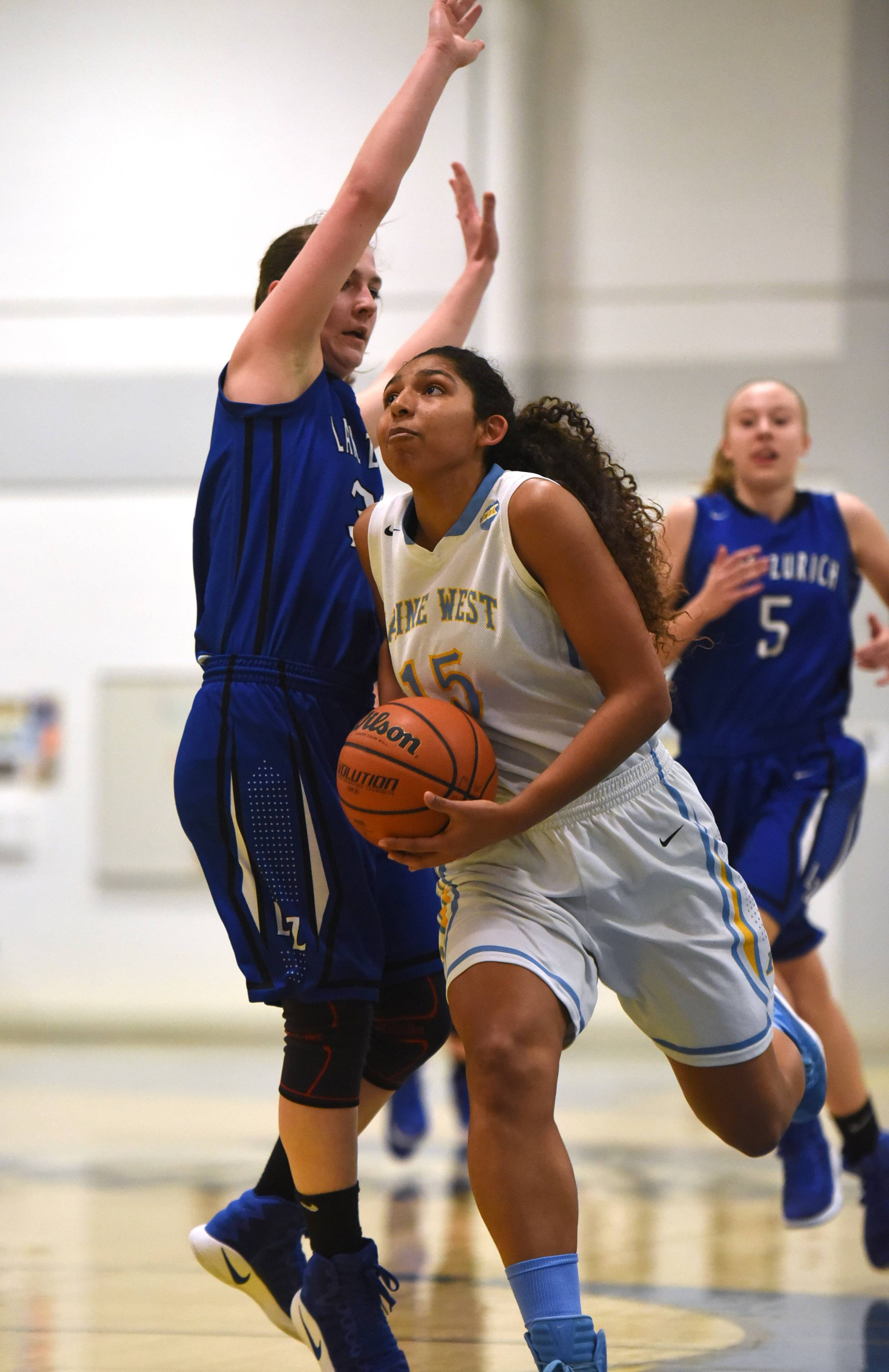 Maine West's Rachel Kent (15) heads to the basket past Lake Zurich's Grace Kinsey during Monday's girls basketball game in Des Plaines.