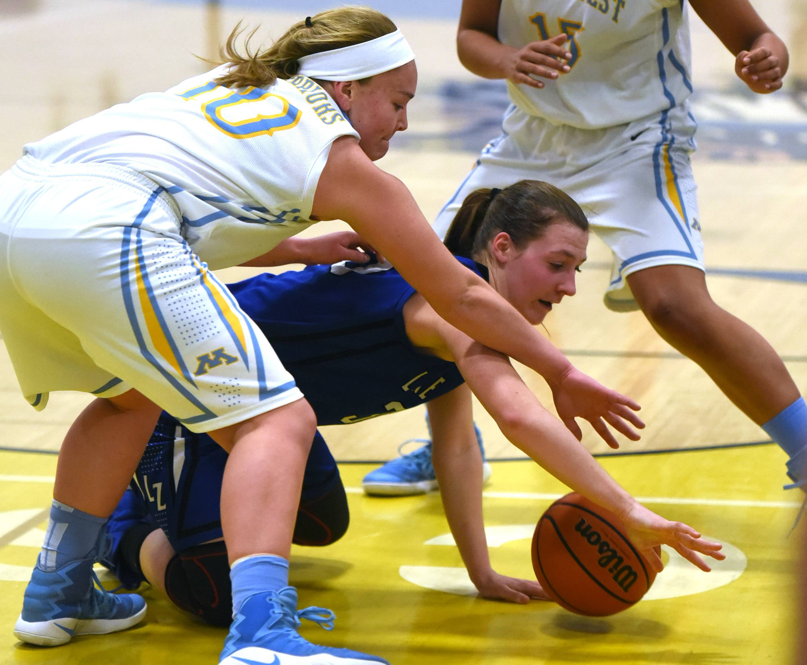 Maine West's Allison Pearson, left, and Lake Zurich's Grace Kinsey chase a loose ball during Monday's game in Des Plaines.