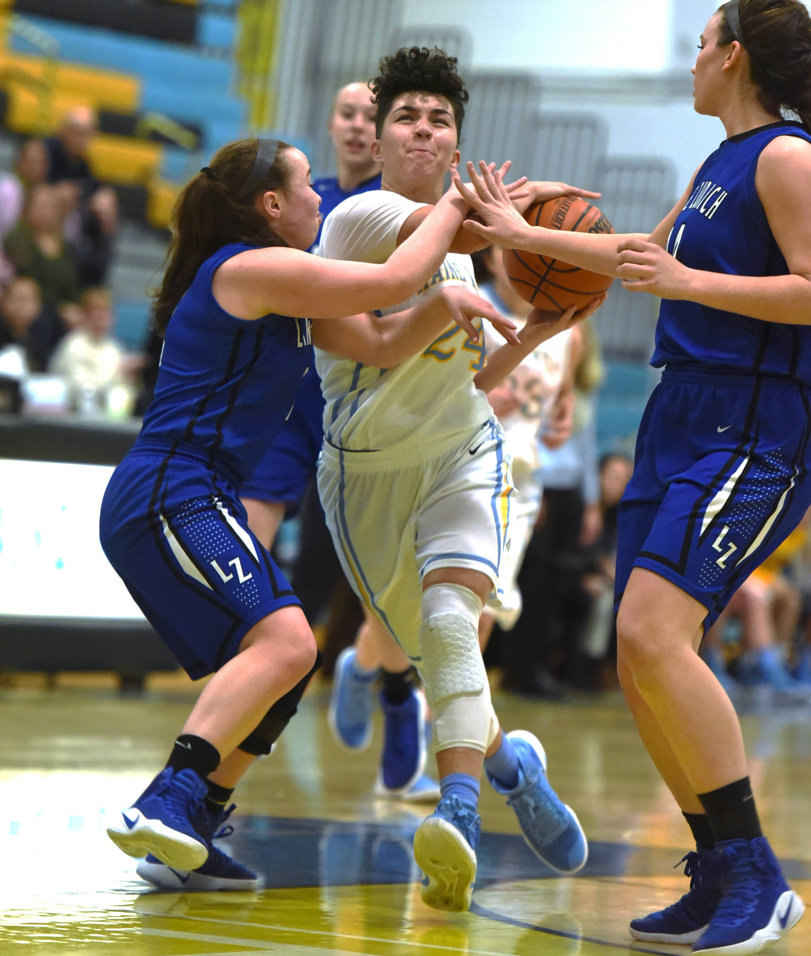 Maine West's Alisa Fallon, center, heads to the basket under heavy defensive pressure during Monday's game against Lake Zurich in Des Plaines.