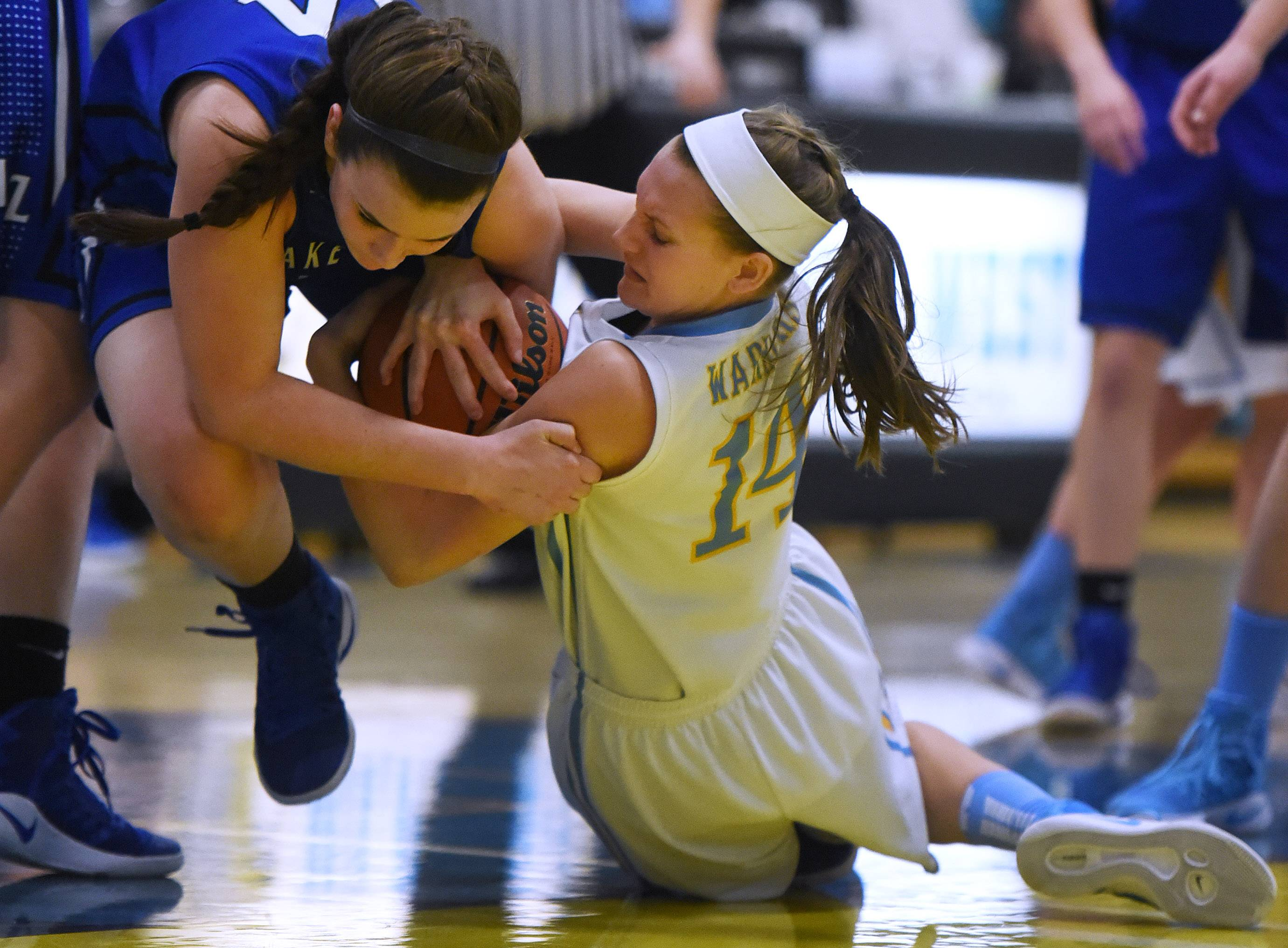 Maine West's Catherine Johnson (14) fights for the ball with Lake Zurich's McKenna Zobel, left, during Monday's game in Des Plaines.