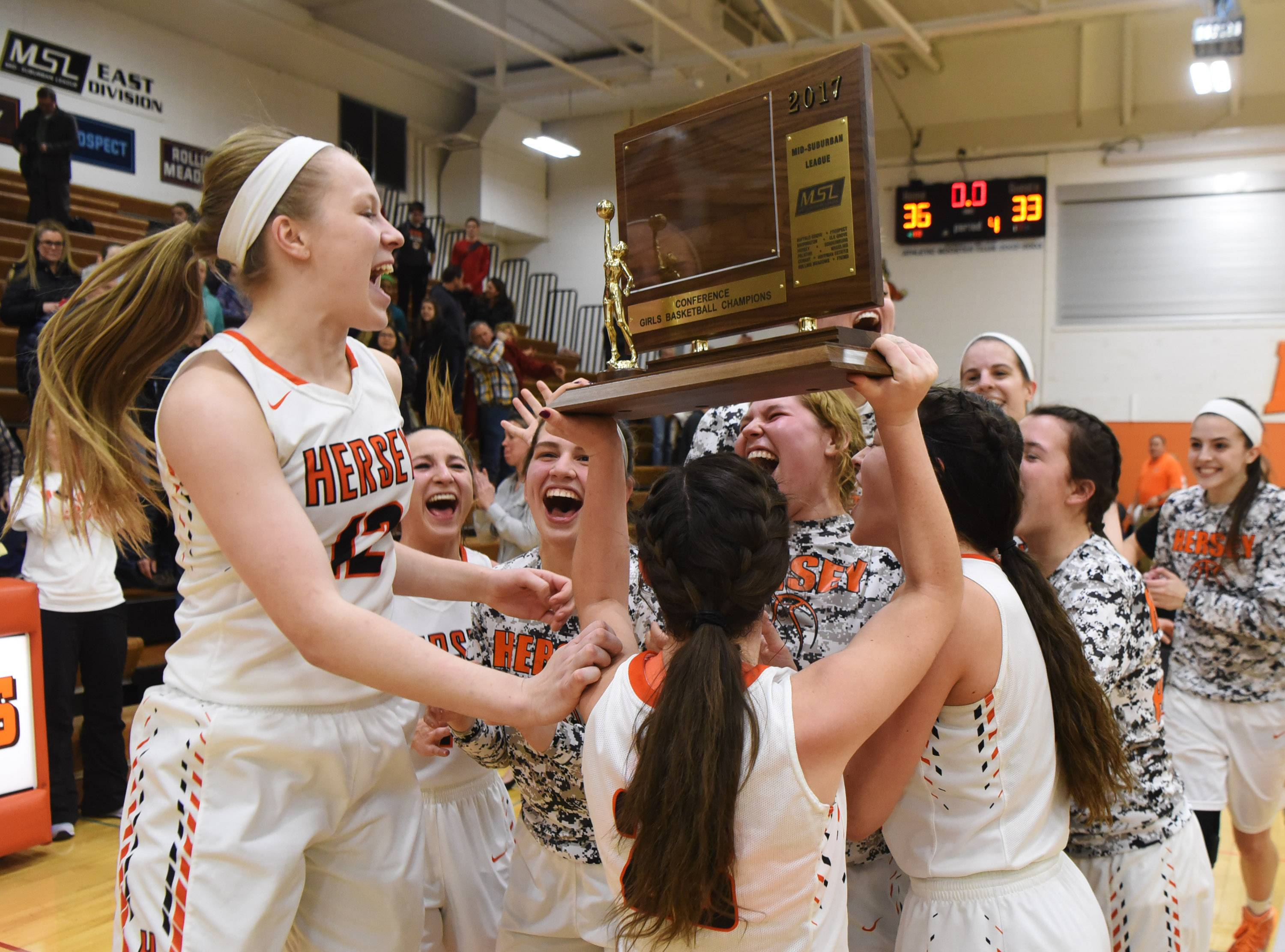Hersey players hold the hardware high after defeating Fremd 36-33 in the Mid-Suburban League championship game in Arlington Heights on Wednesday.