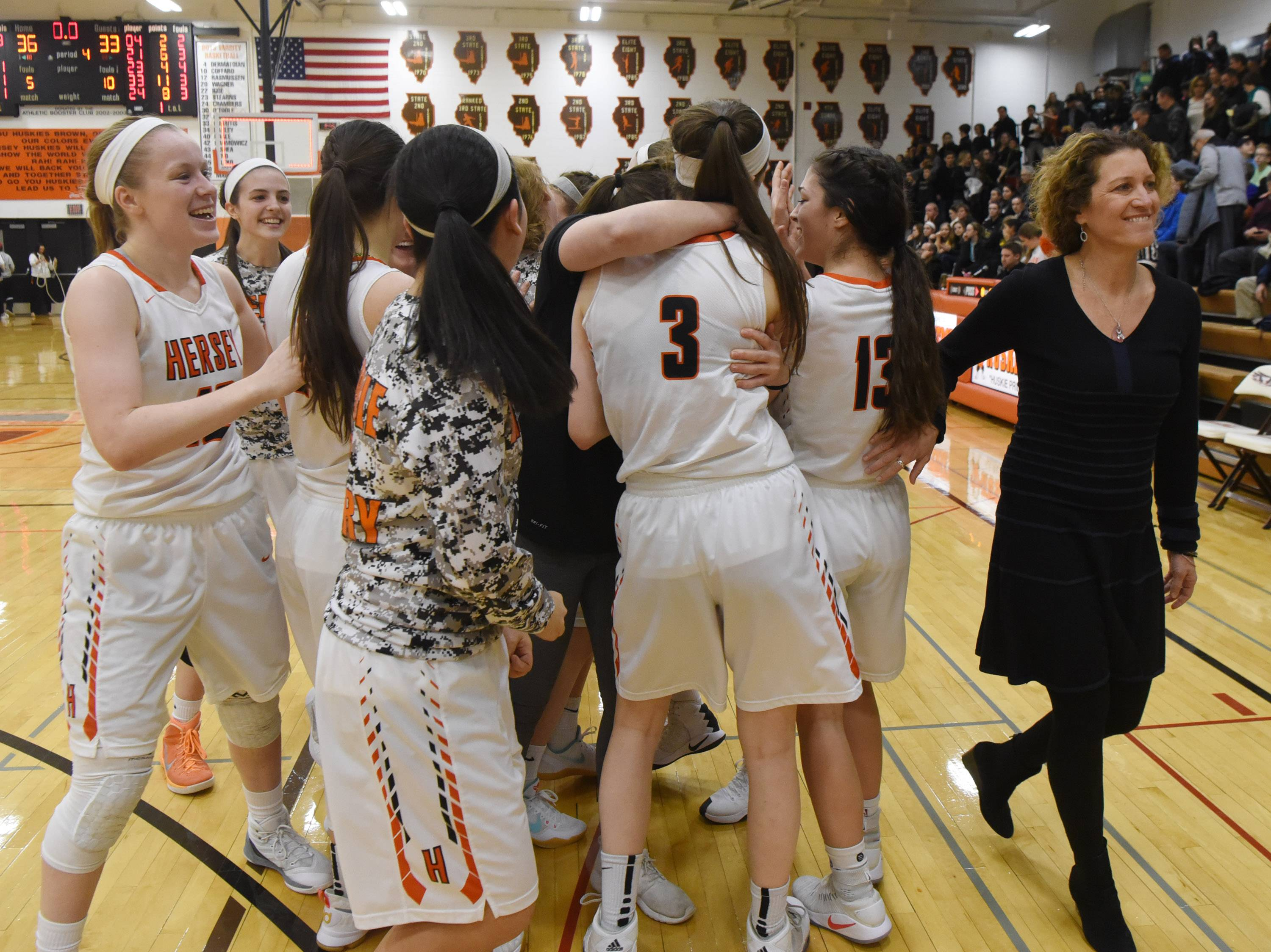 Hersey players and coach Mary Fendley celebrate their 36-33 victory over Fremd during the Mid-Suburban League championship game in Arlington Heights on Wednesday.