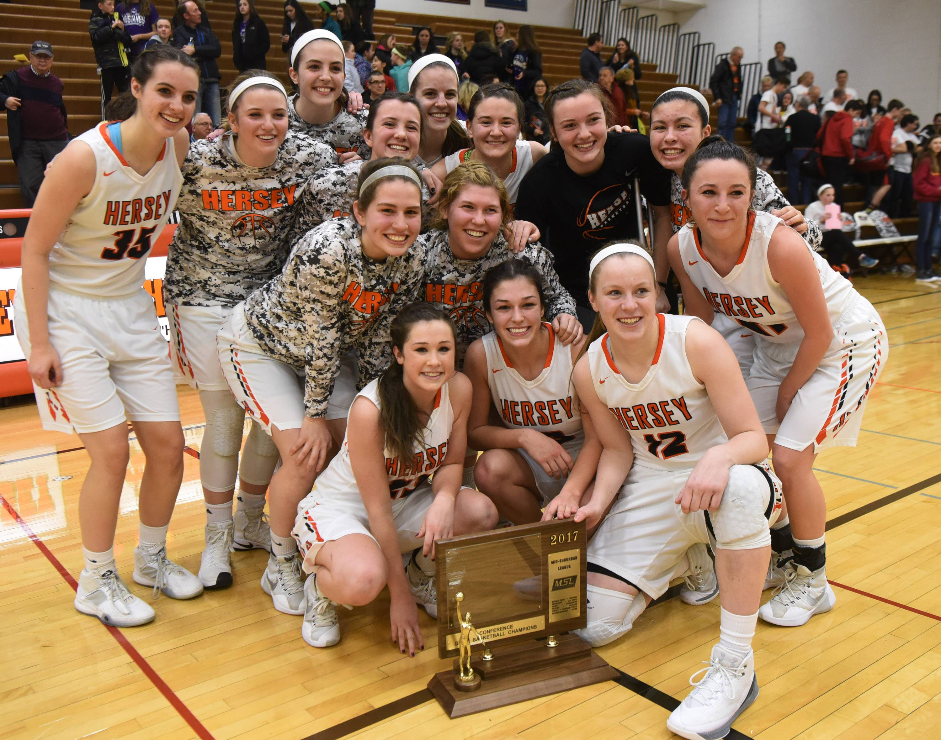 Hersey players pose with their trophy after defeating Fremd 36-33 during the Mid-Suburban League championship game in Arlington Heights on Wednesday.