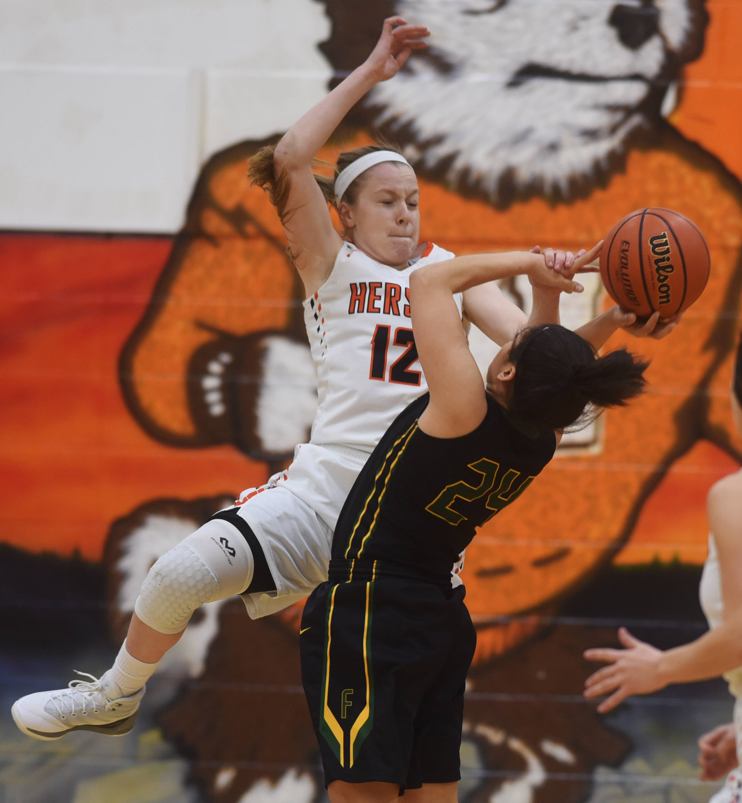Hersey's Claire Gritt, left, fouls Fremd's Midori Williams during the Mid-Suburban League championship game in Arlington Heights on Wednesday.