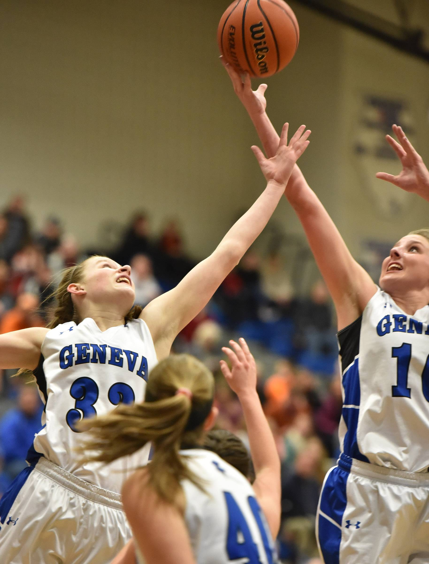 Geneva teammates Madison Mallory and Grace Loberg stretch for a rebound against St. Charles East Friday in Geneva.