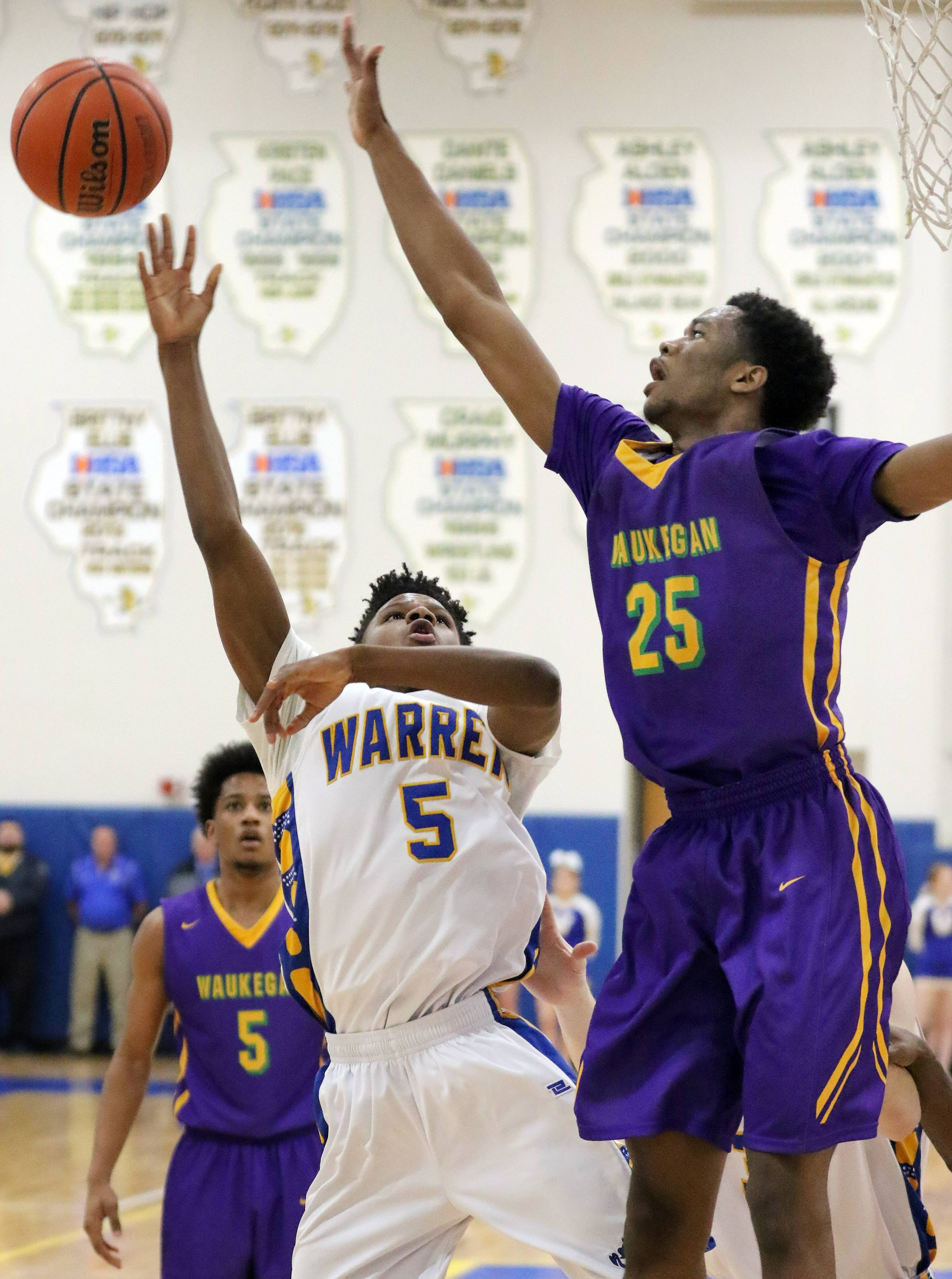 Warren's Juwan Perry, left, shoots over Waukegan's Bryant Brown on Tuesday night in Gurnee.