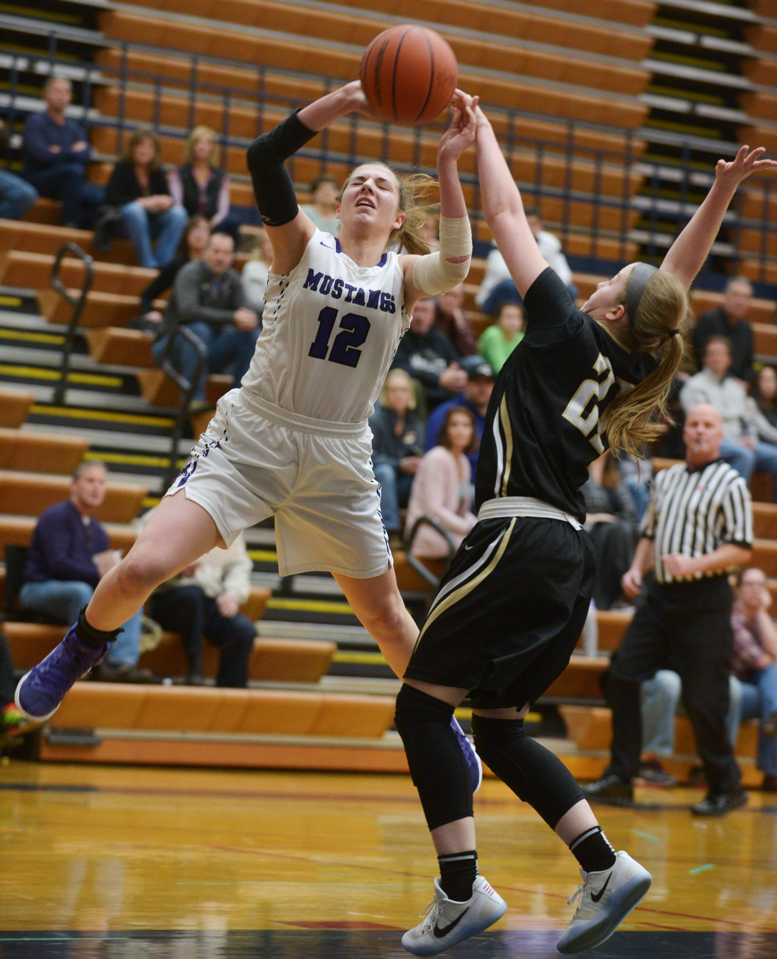 Rolling Meadows' Morgan Campagna, left, gets fouled by Glenbard North's Leah Miller on a drive to the basket during the Conant regional semifinal on Tuesday.