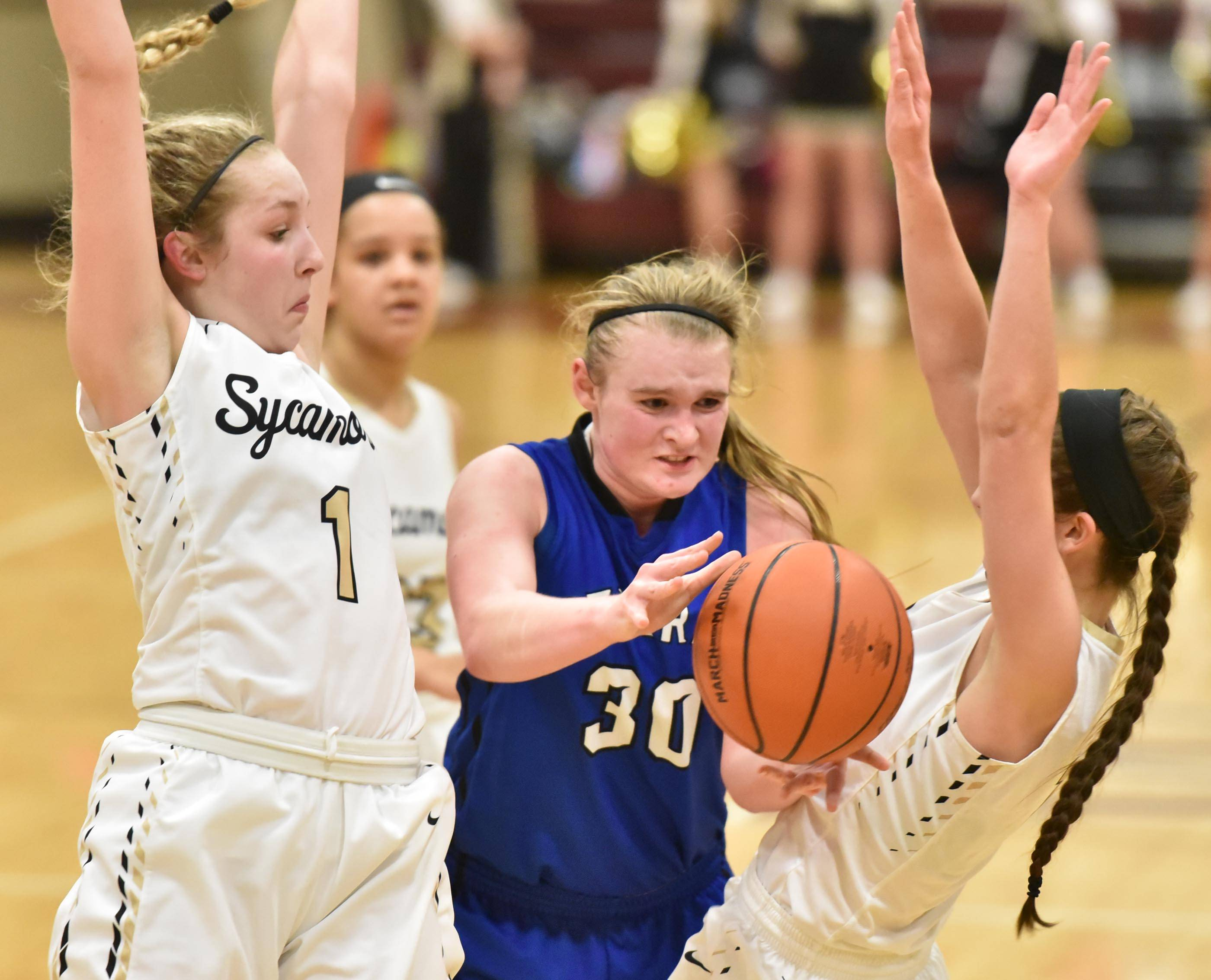 Burlington Central's Kathryn Schmidt passes the ball under pressure from Sycamore's Kylie Feuerbach and Taryn Mathey in the girls basketball regional playoff game at Wheaton Academy Wednesday.