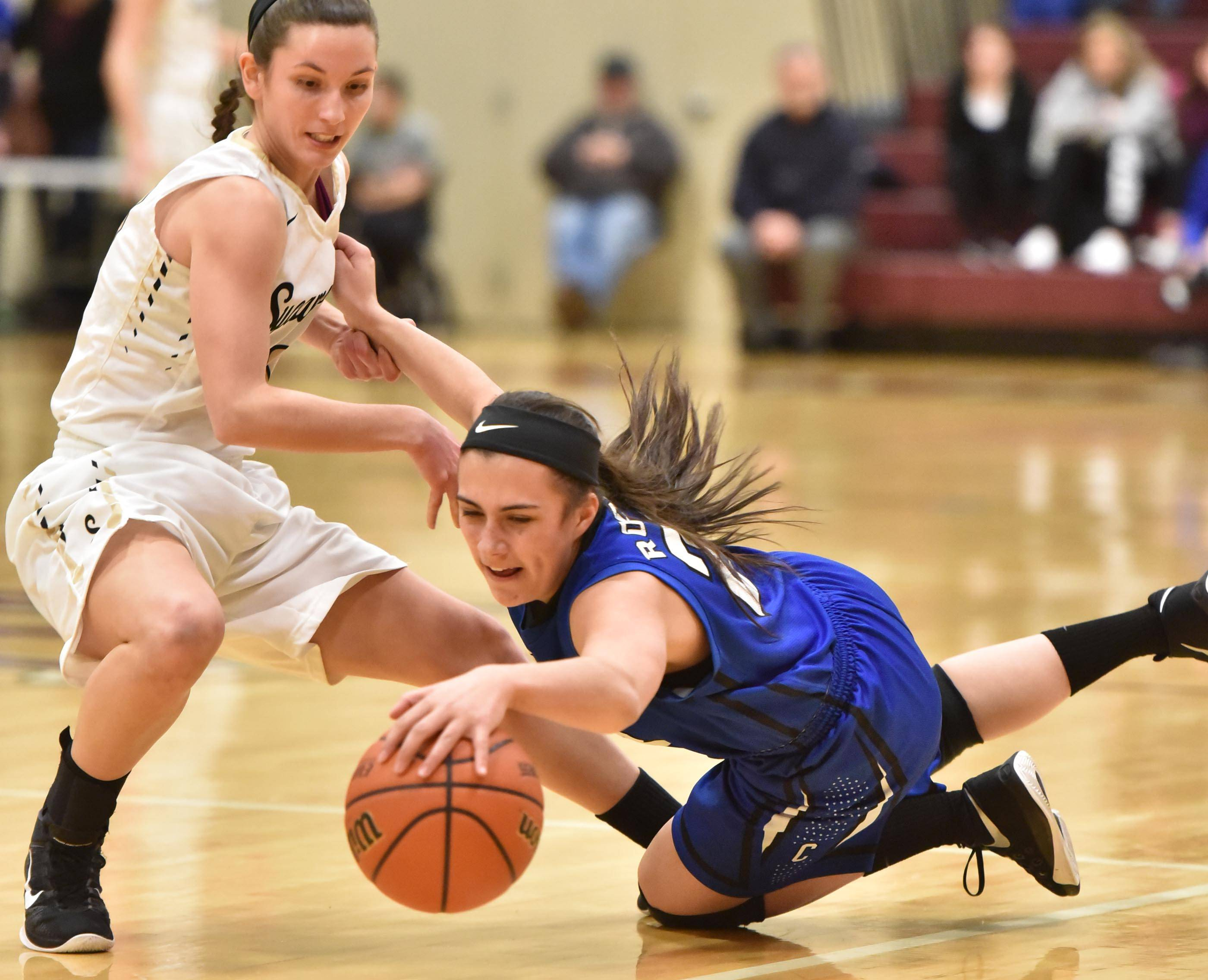 Burlington Central's Maddie Drescher dives for a loose ball as Sycamore's Taryn Mathey defends in the girls basketball regional playoff game at Wheaton Academy Wednesday.