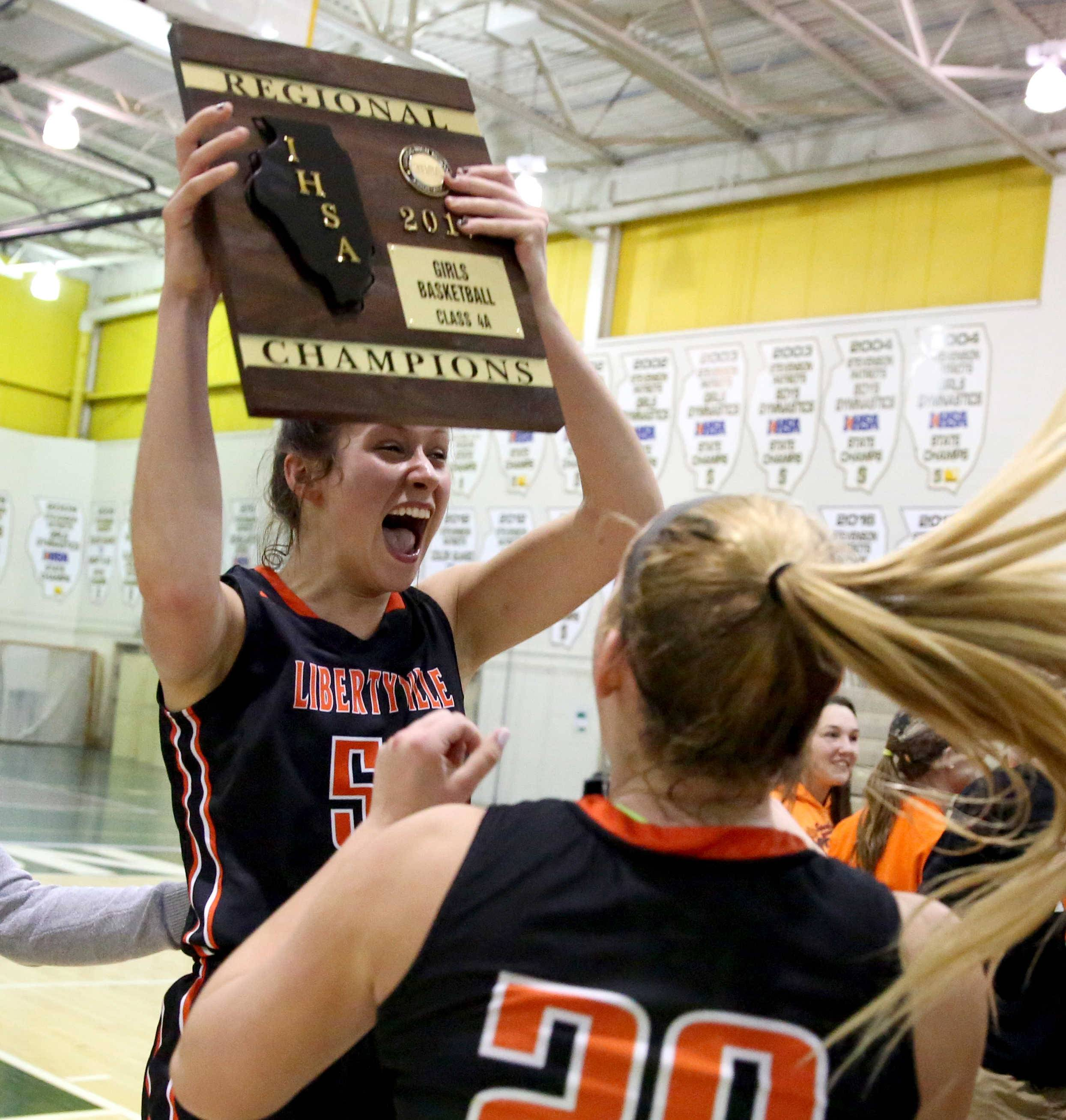 Libertyville's Claire Keefe hoists the hardware high after a win over Stevenson in Class 4A regional final play Friday at Stevenson. Libertyville won 35-33.