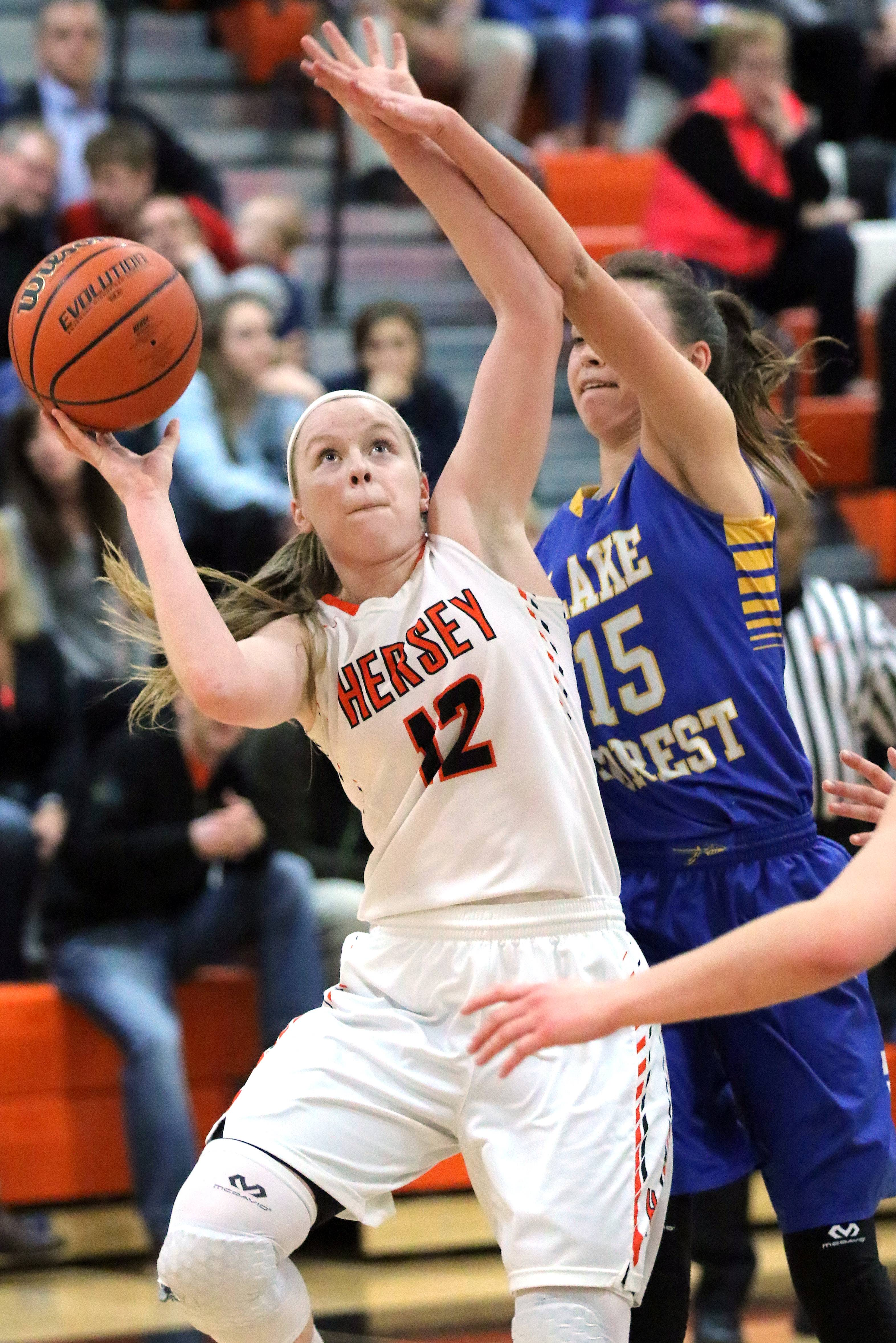Hersey's Claire Gritt (12) drives on Lake Forest's Halle Douglass during Class 4A sectional semifinal play Monday night at Libertyville.