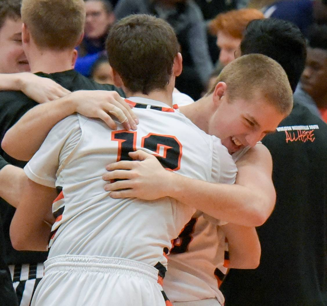 Wheaton Warrenville South's Chase Stebbins and Matt Dohse celebrate the Tigers' 38-35 win over the Naperville North Huskies during boys varsity basketball Wednesday in Wheaton.