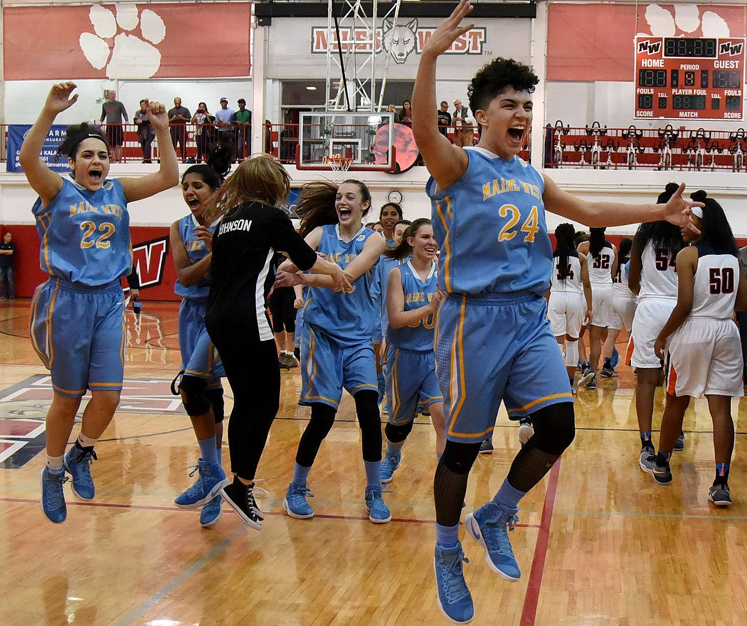 Maine West's Alisa Fallon, right and Bianca Mando jump for joy with teammates after the Warriors defeated Evanston in the Class 4A sectional final at Niles West on Thursday night.