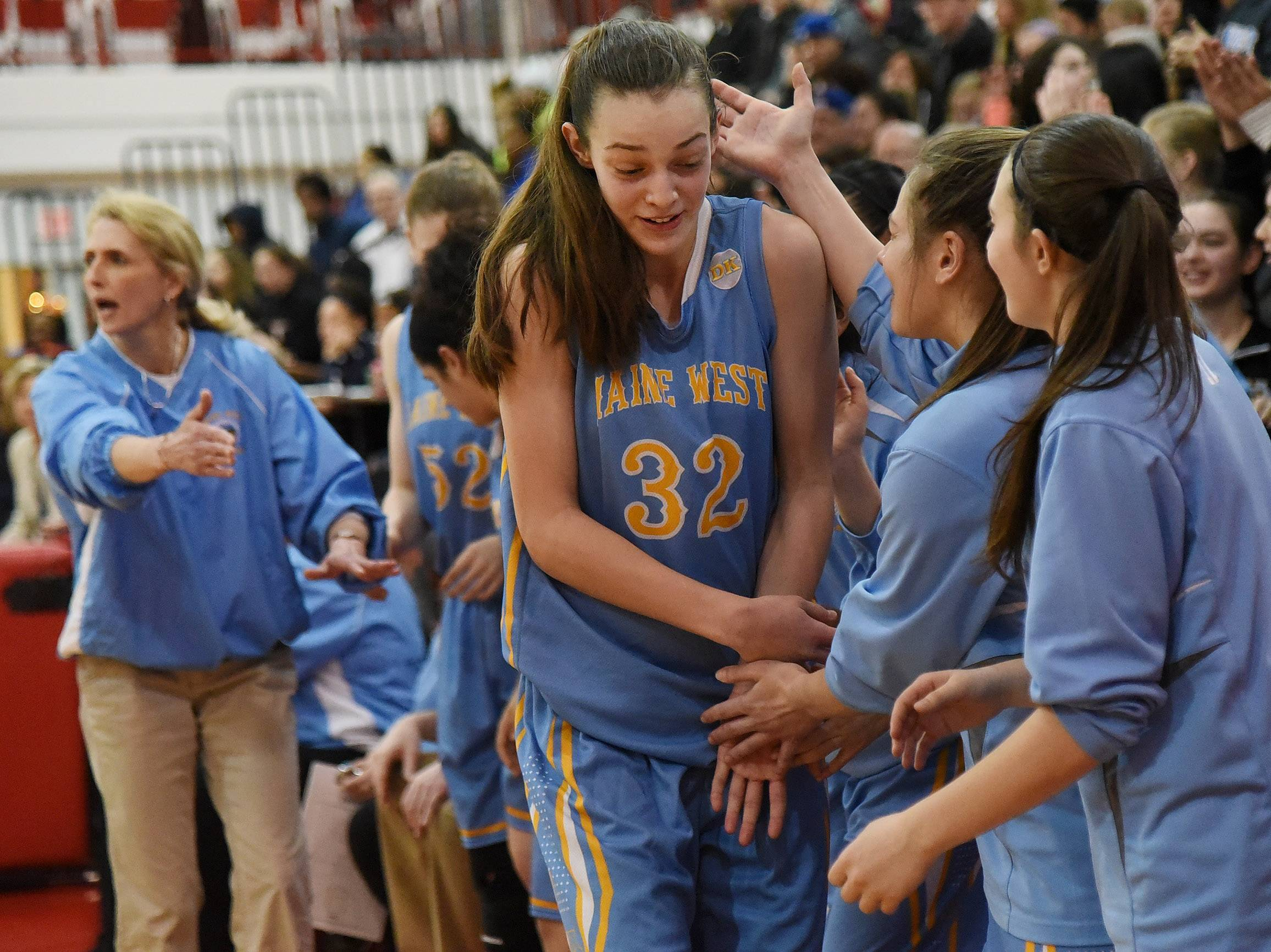 Maine West's Angela Dugalic is mobbed by her teammates after coming out of the game in the final minutes against Evanston in the Class 4A sectional final at Niles West on Thursday night.