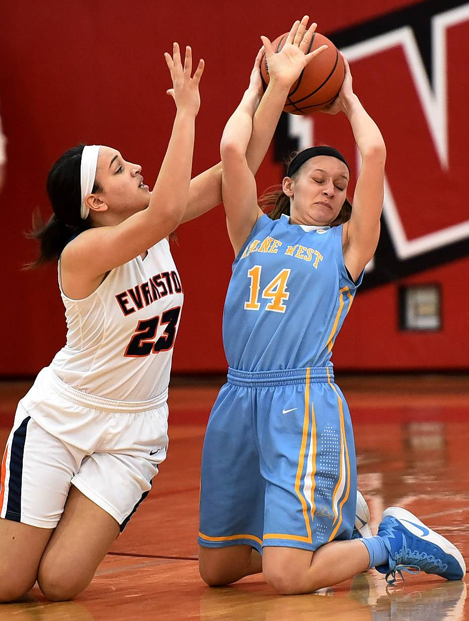 Maine West's Catherine Johnson battles for the ball with Evanston's Leighah-Amori Wool during Class 4A sectional final play at Niles West on Thursday night.
